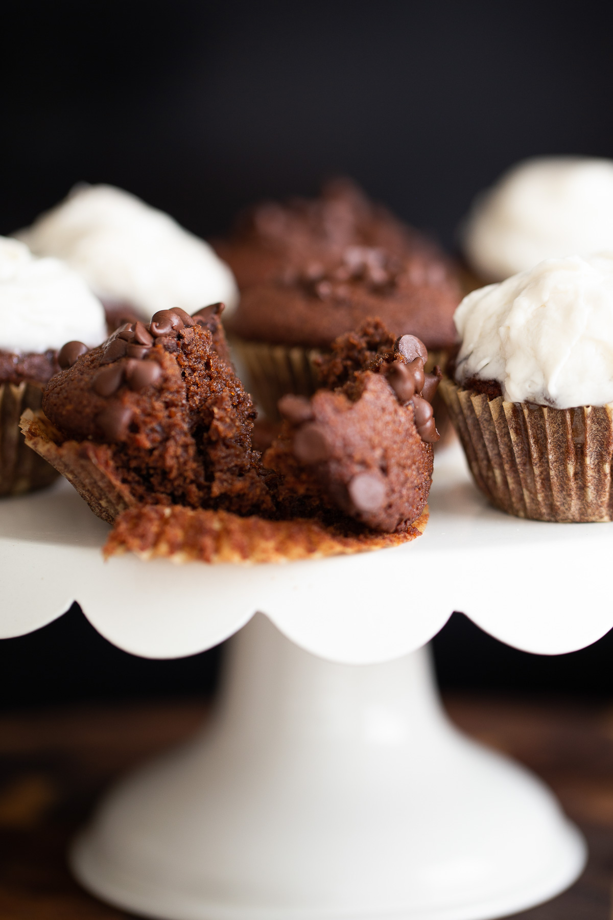 moist vegan glutenfree chocolate muffin on a cake stand broken in half to reveal moist crumb
