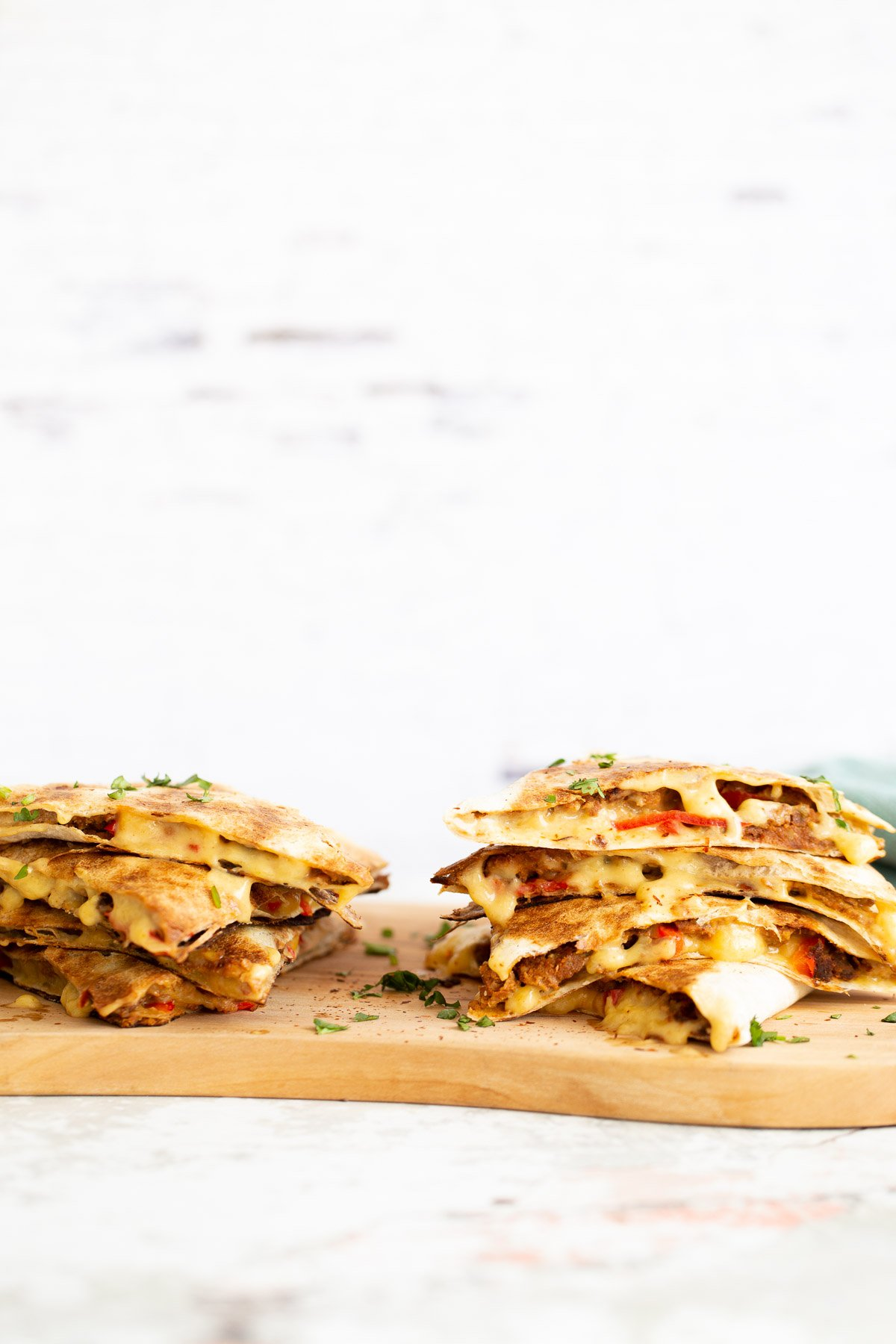 two stacks of quesadillas filled with vegan walnut taco meat on a chopping board