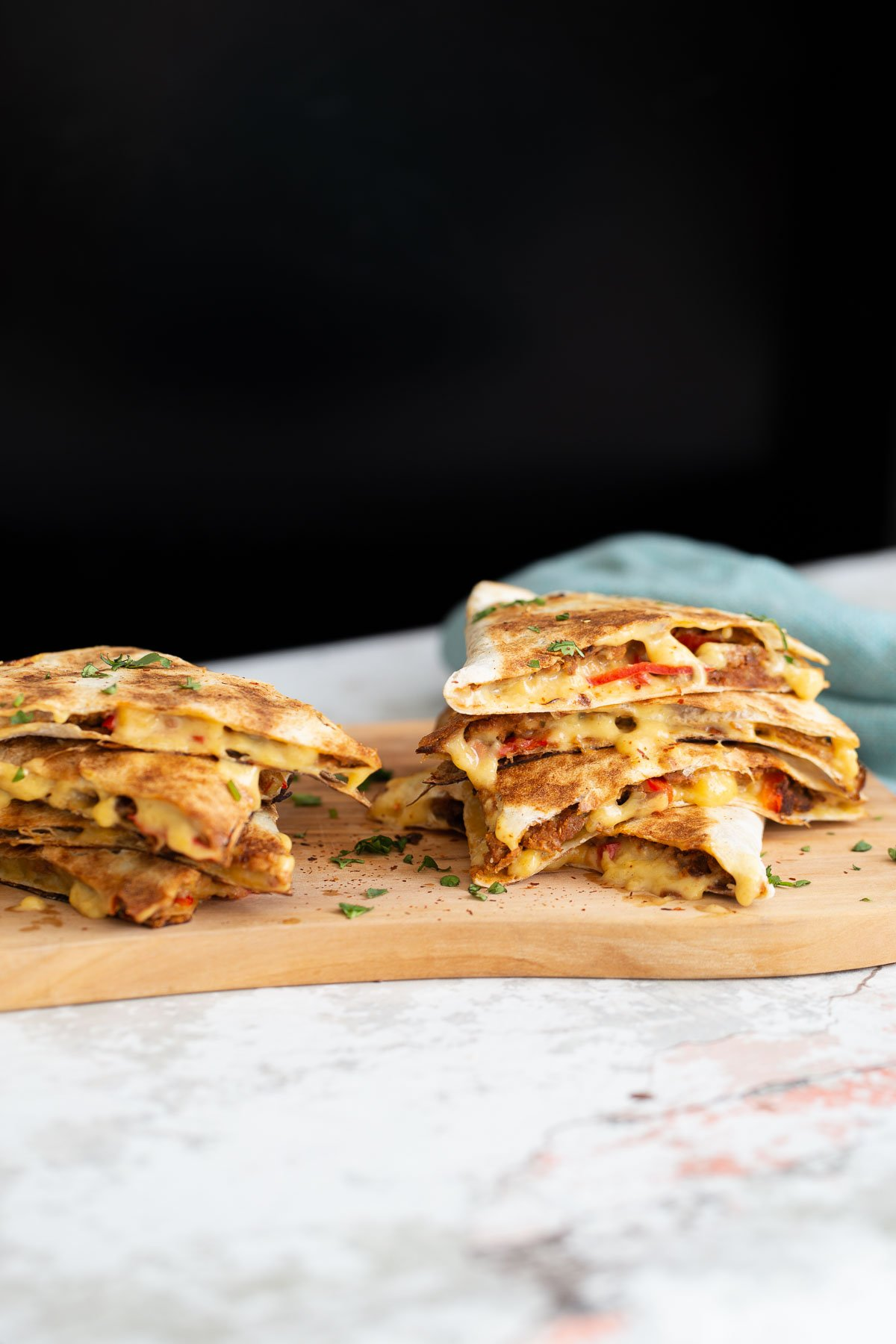 side view of vegan quesadillas filled with vegan walnut taco meat, bell pepper and melted cheese