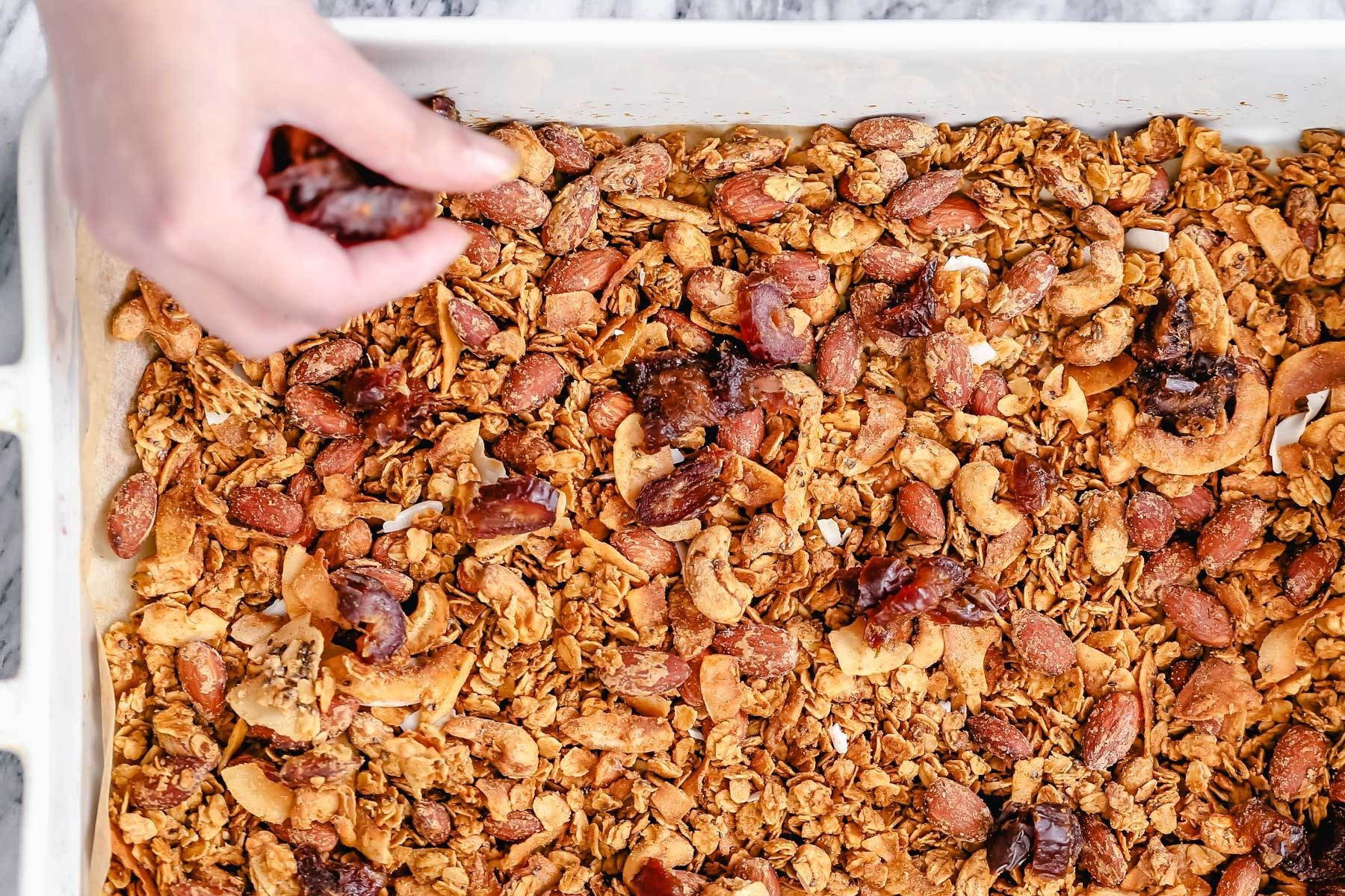 baked vegan granola being spread out in a casserole dish