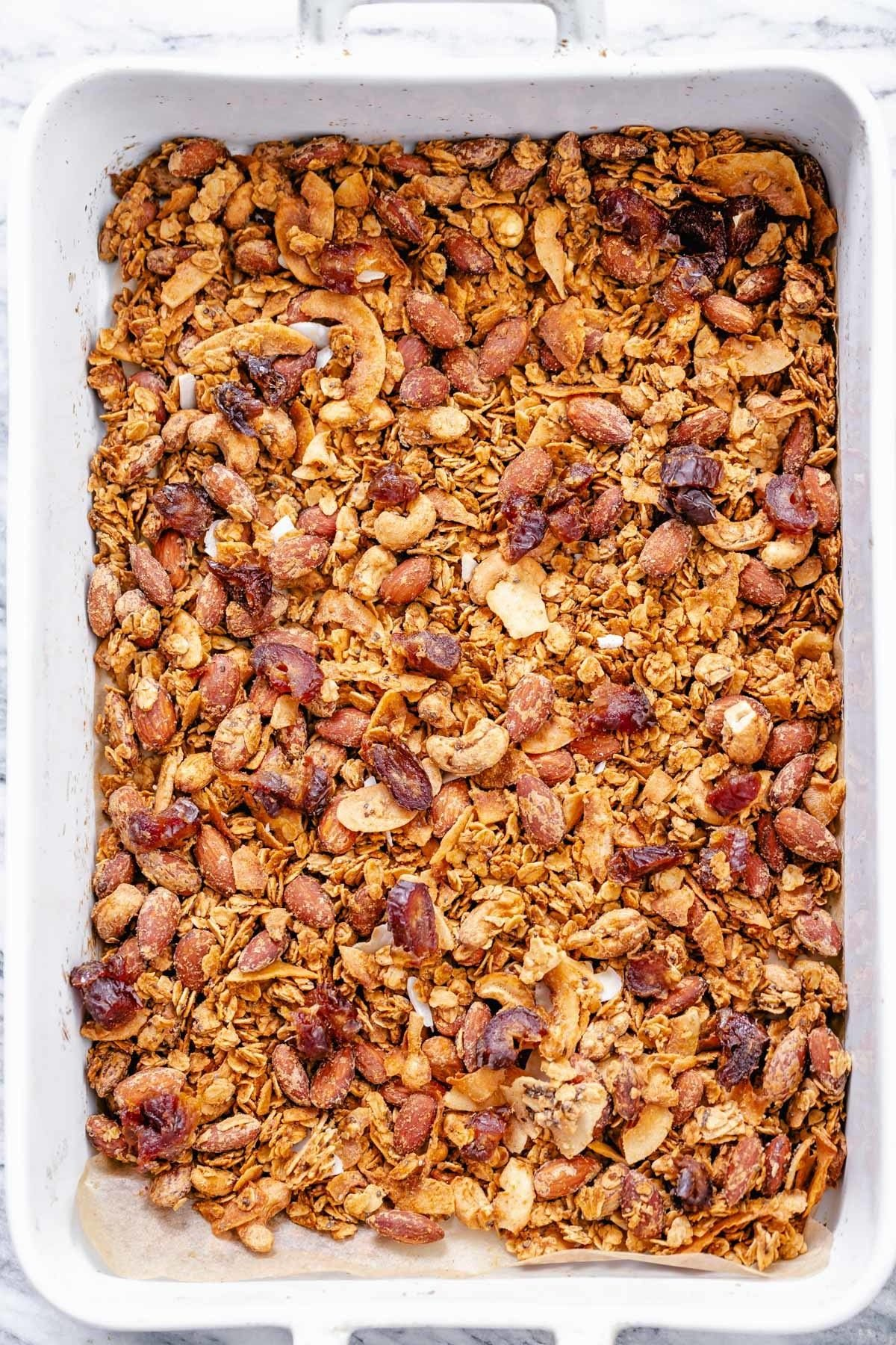 overhead shot of vegan baked coconut almond granola in a casserole dish