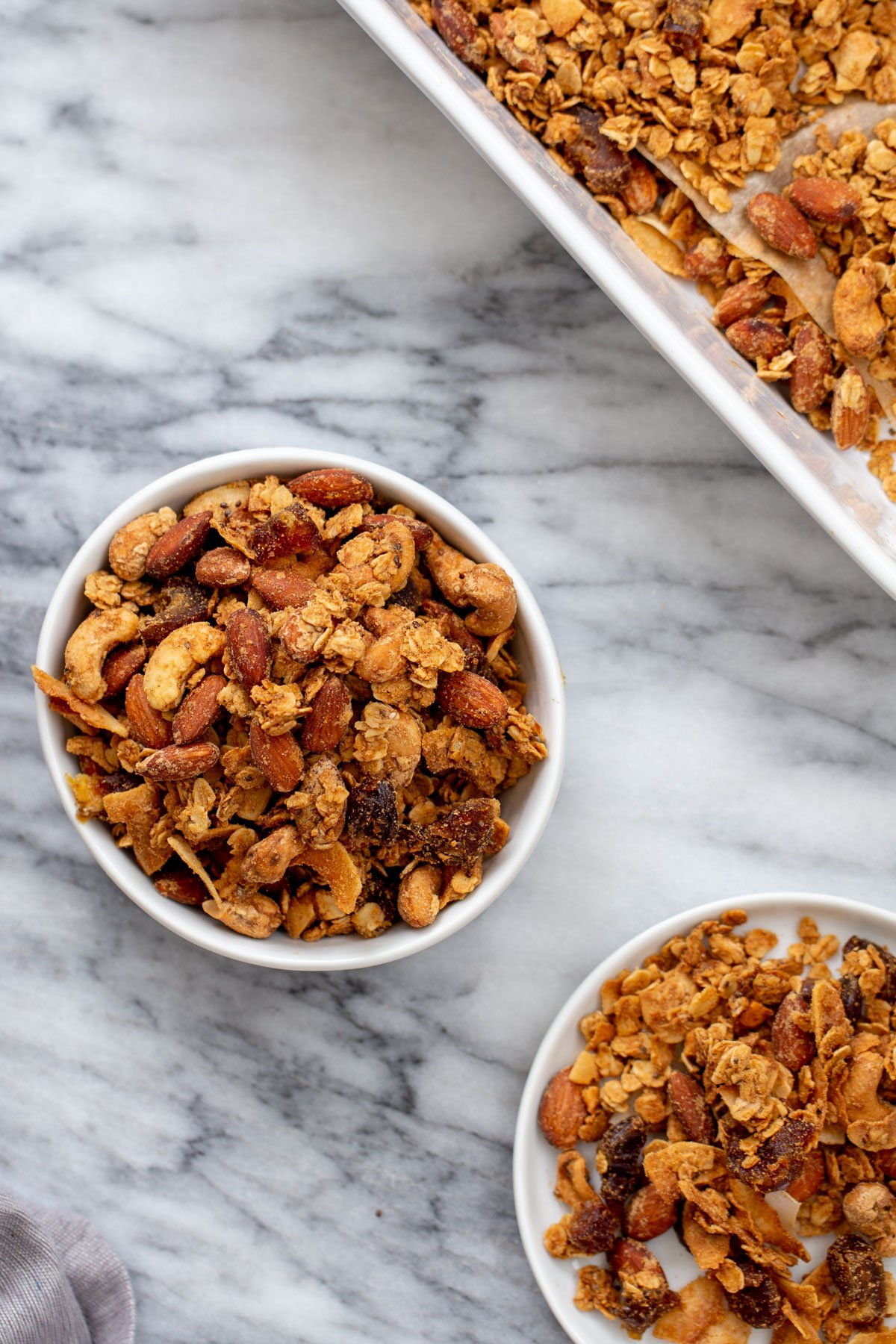 two small bowls of vegan almond coconut granola on a marble countertop