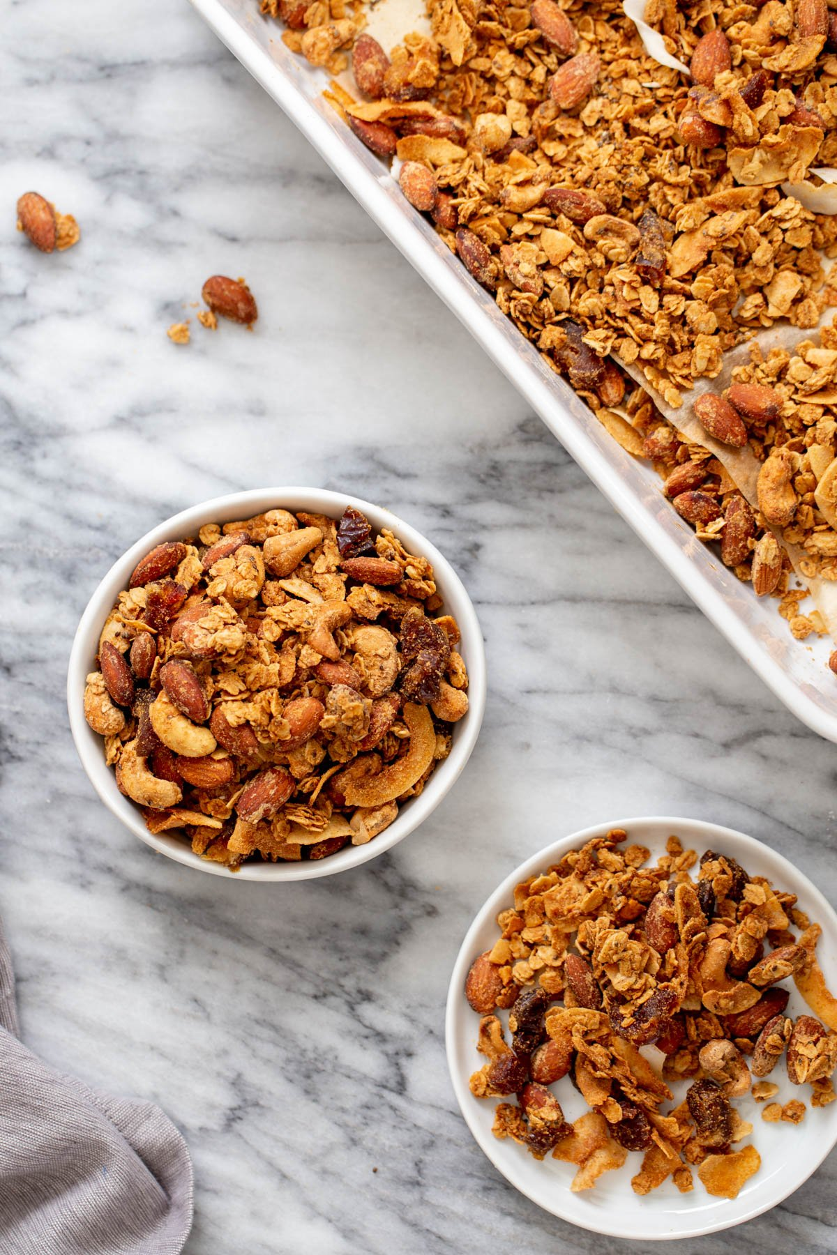 two small bowls of homemade baked vegan almond coconut granola next to a baking sheet with granola
