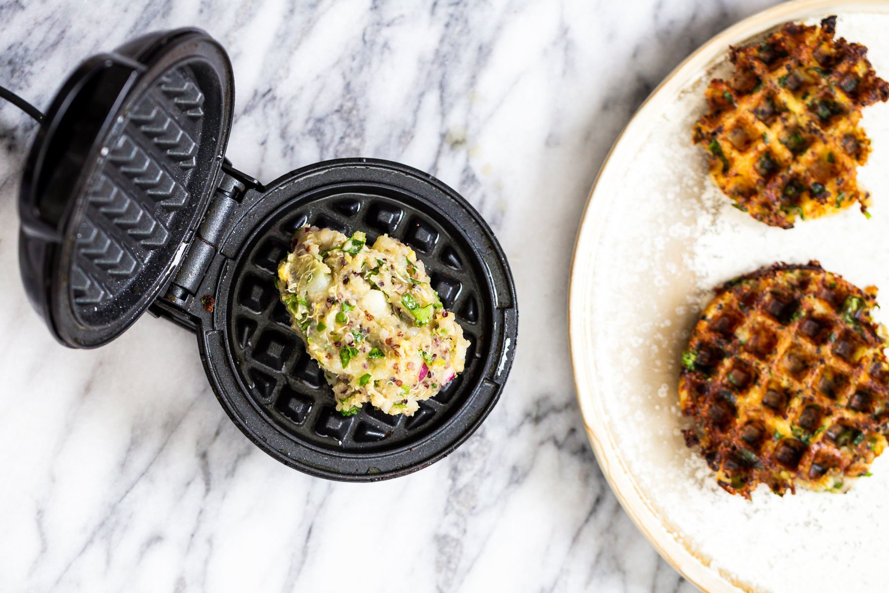 Indian spiced crispy vegan potato quinoa waffles being baked in a waffles iron