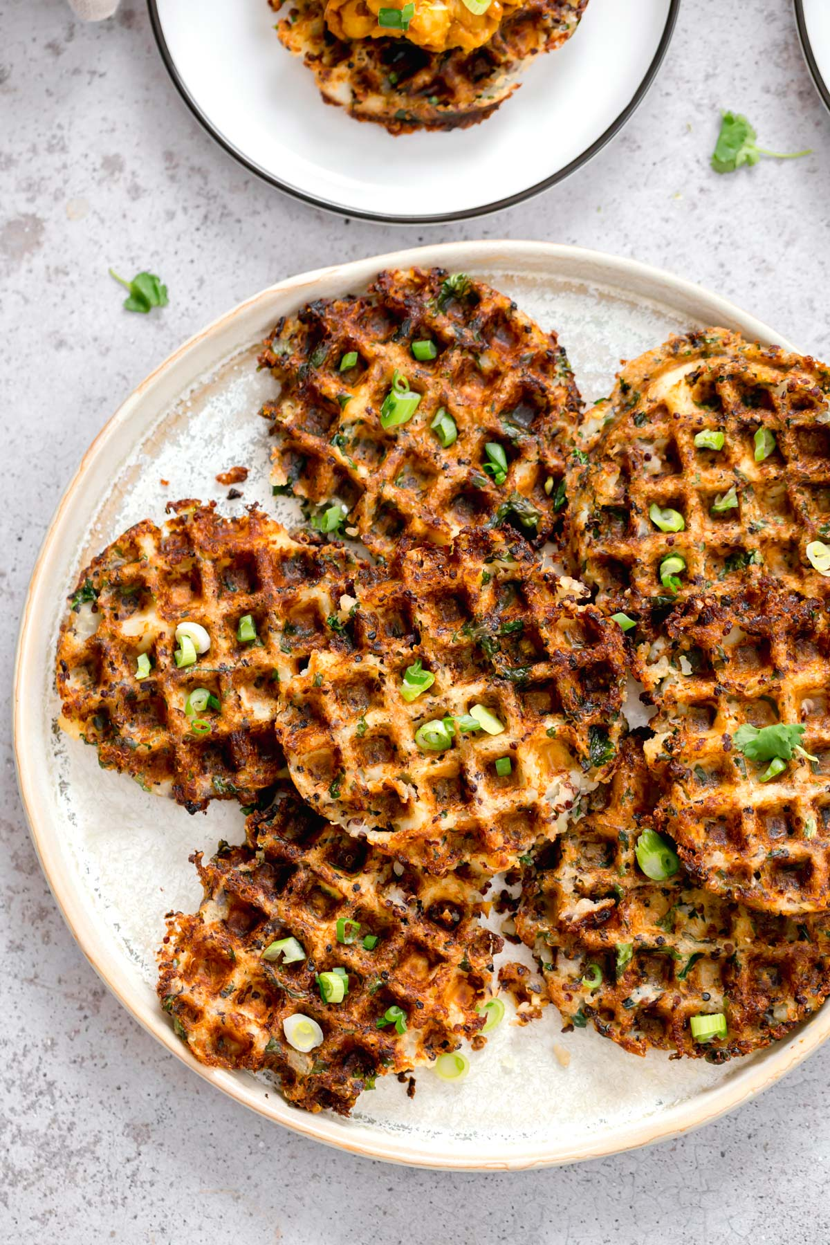 crispy vegan potato quinoa waffles topped with chopped chives