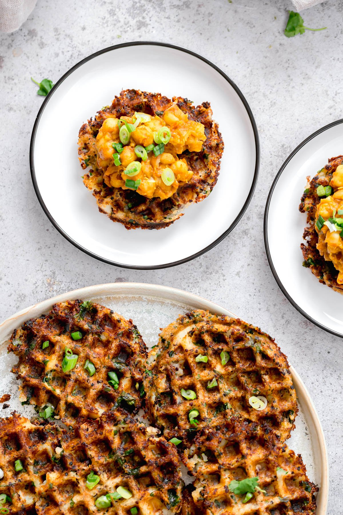 vegan quinoa potato waffles topped with chopped chives and smashed chickpeas
