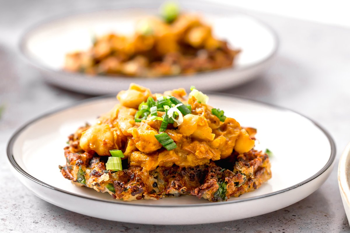 side view of a vegan potato quinoa waffle being topped with smashed chickpeas