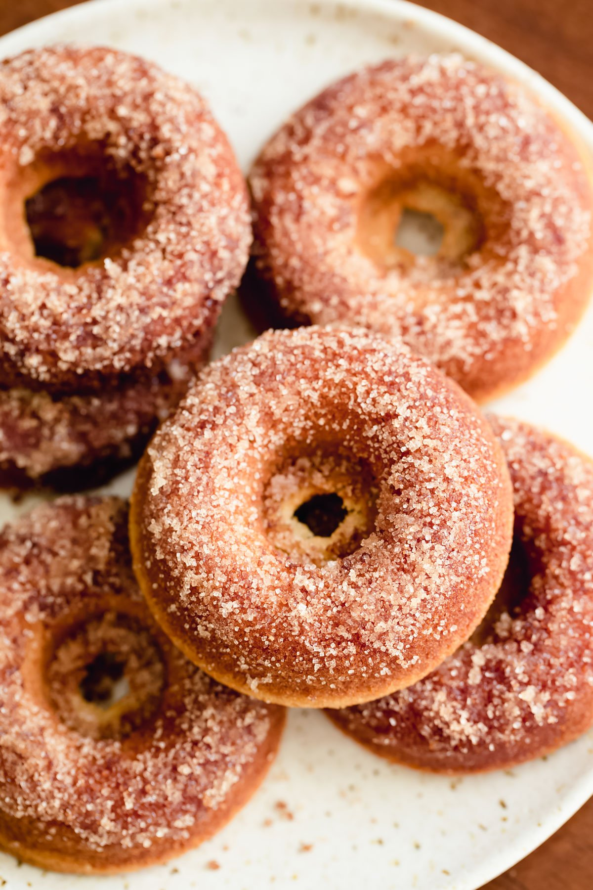 a plate of glutenfree vanilla donuts with coated with cinnamon sugar