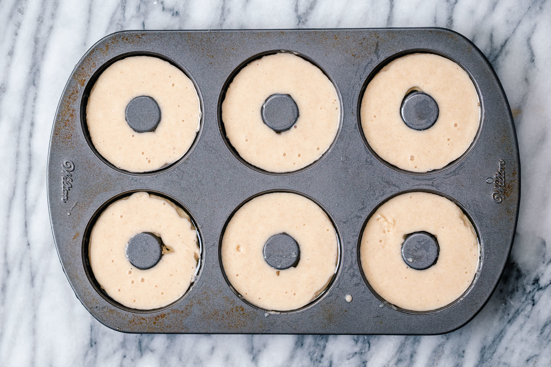 glutenfree almond flour donuts batter being filled into donuts pan