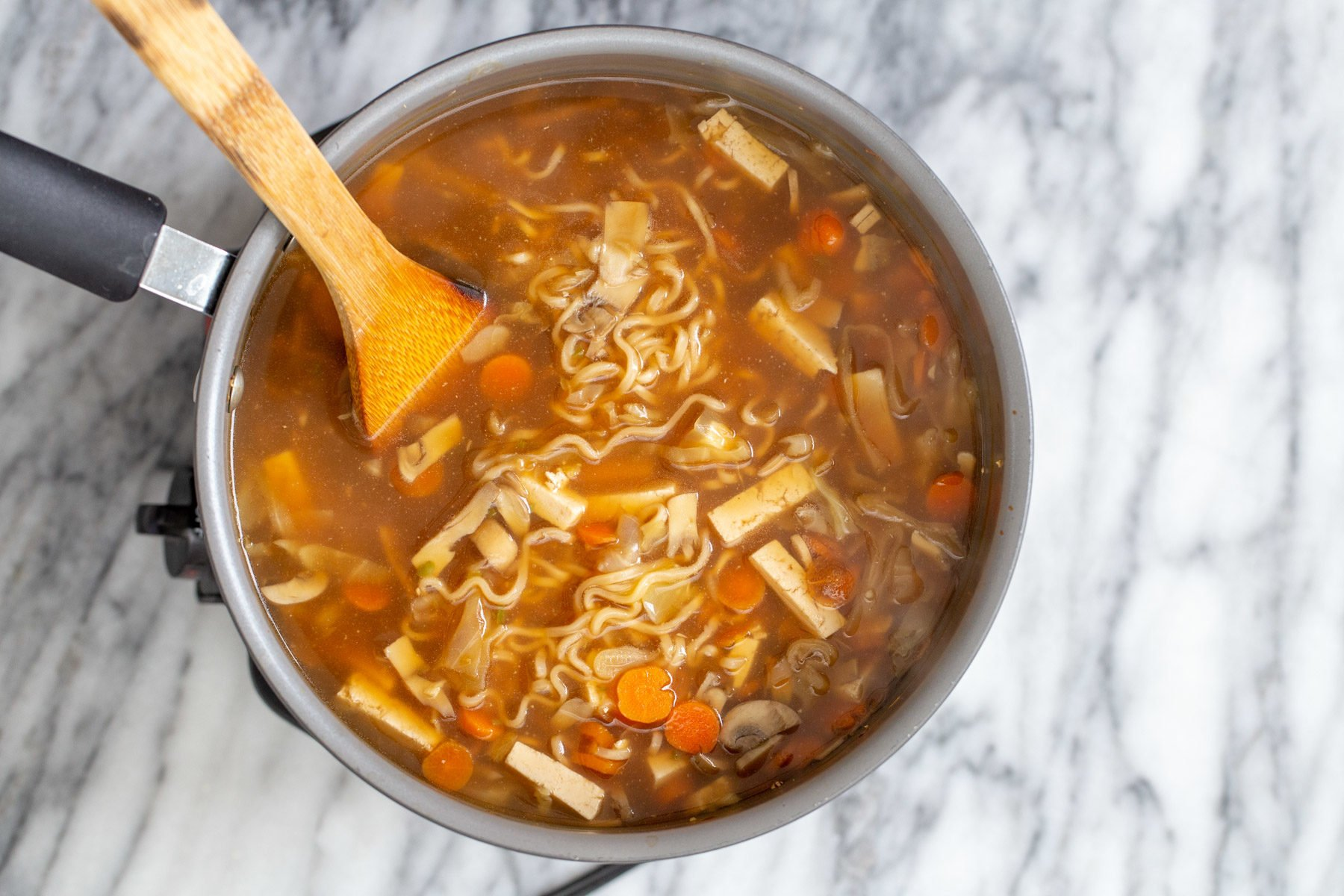 vegan hot and sour soup with ramen noodles in a silver soup pot with a wooden spoon