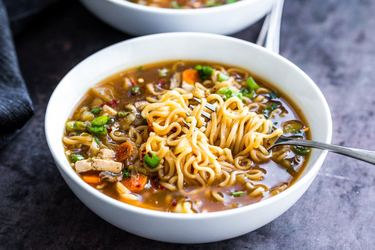 a fork twirling some ramen noodles in a bowl of hot and sour soup