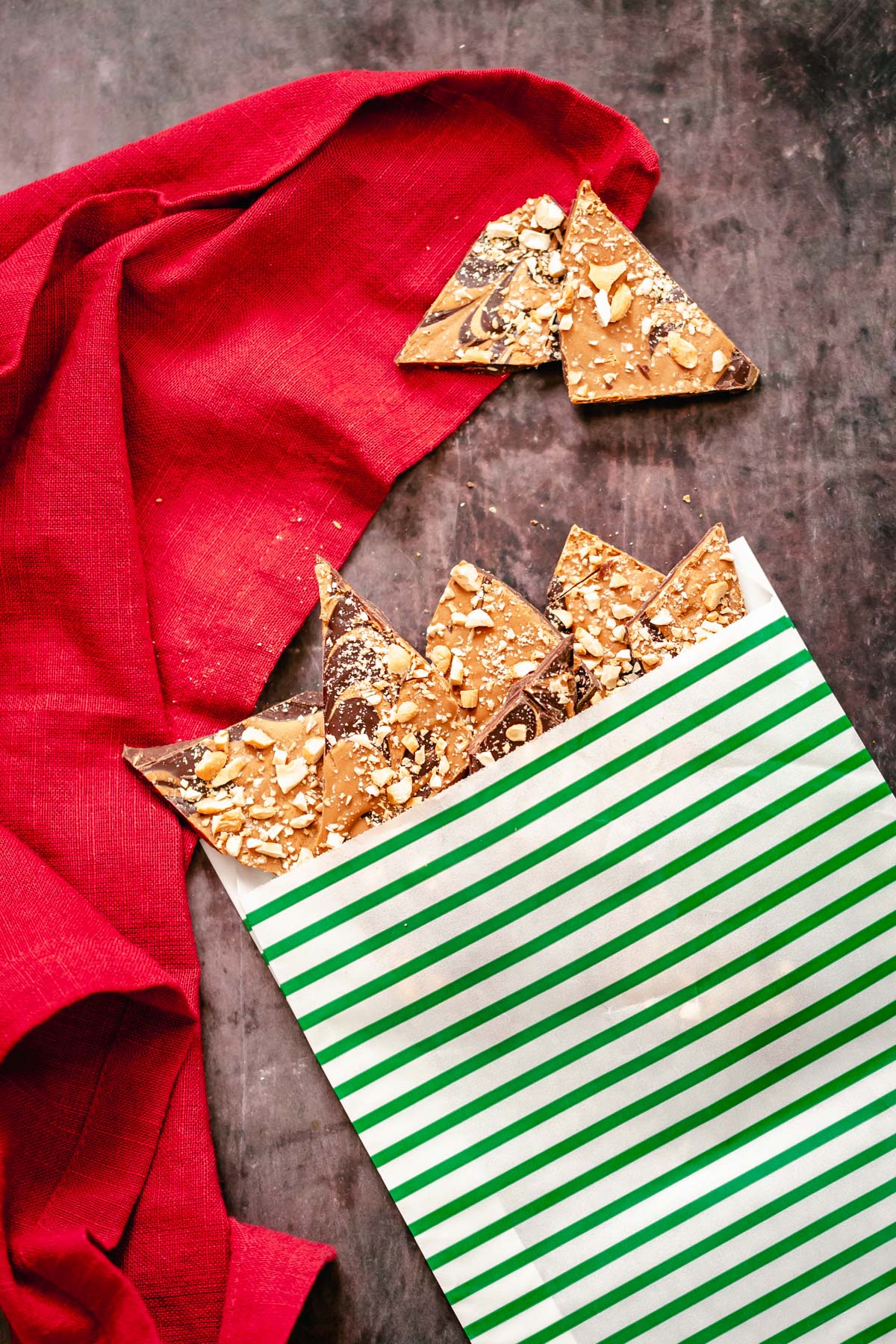 homemade vegan peanut butter cup chocolate bark in a green and white Christmas paper bag