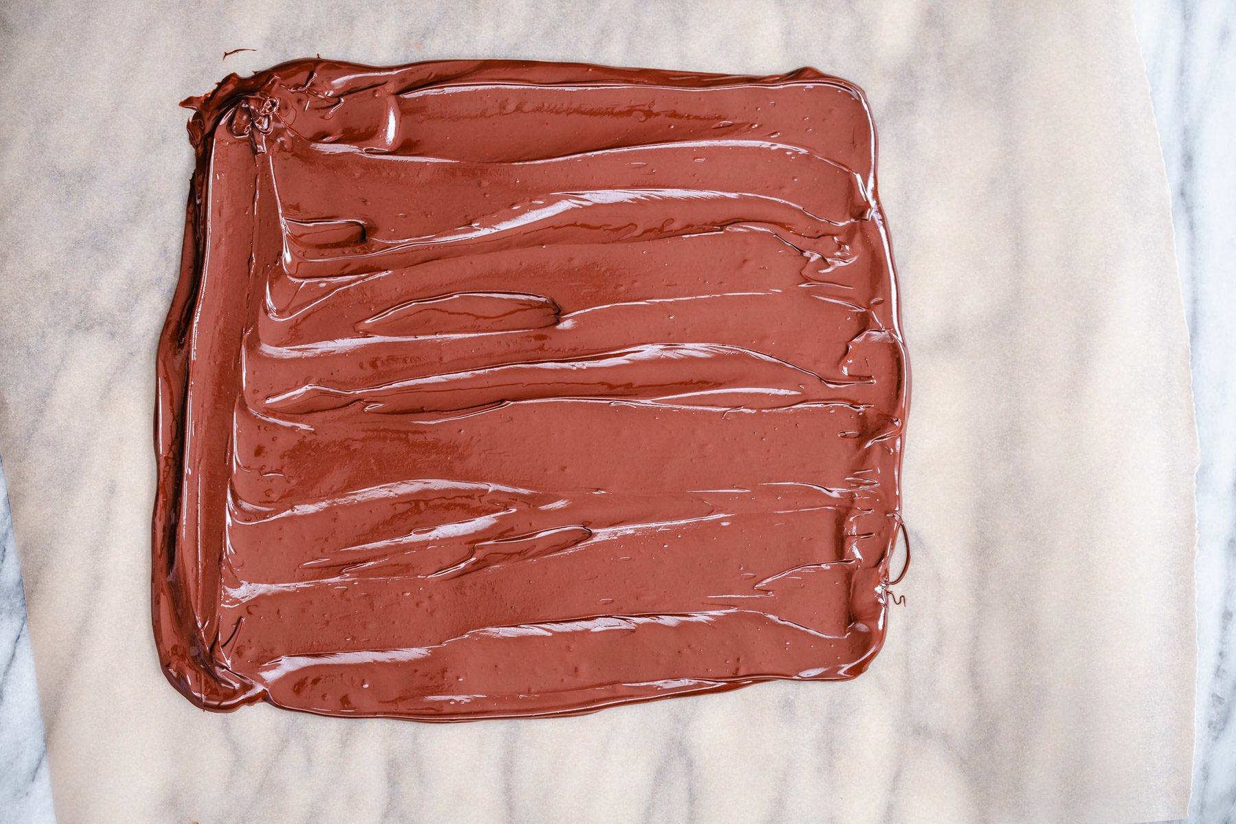 melted chocolate being spread out into a rectangle to make chocolate bark