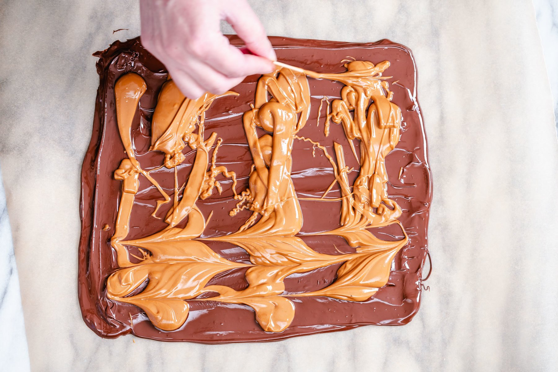 melted peanut butter being swirled into a rectangle of melted chocolate to make chocolate bark