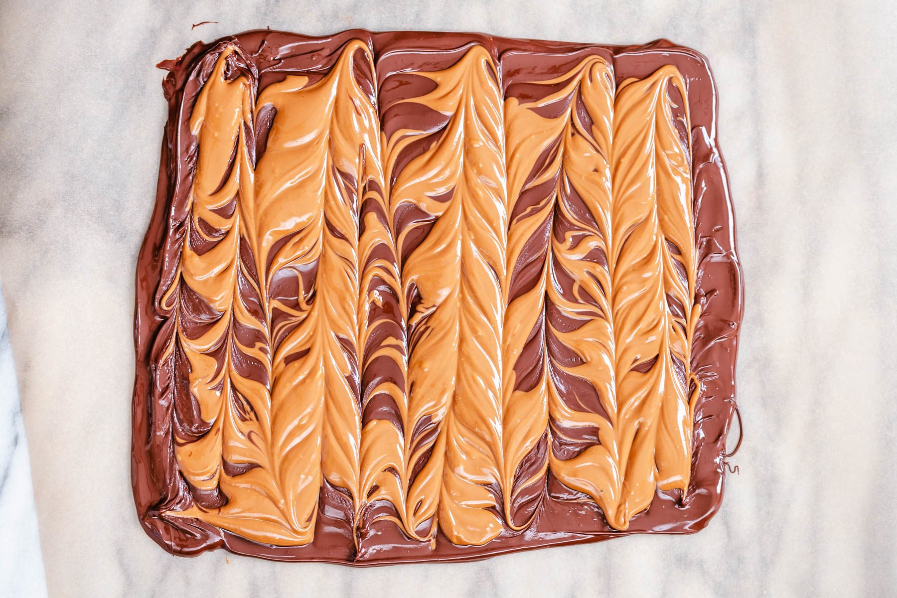 peanut butter cup chocolate bark on a sheet of parchment paper