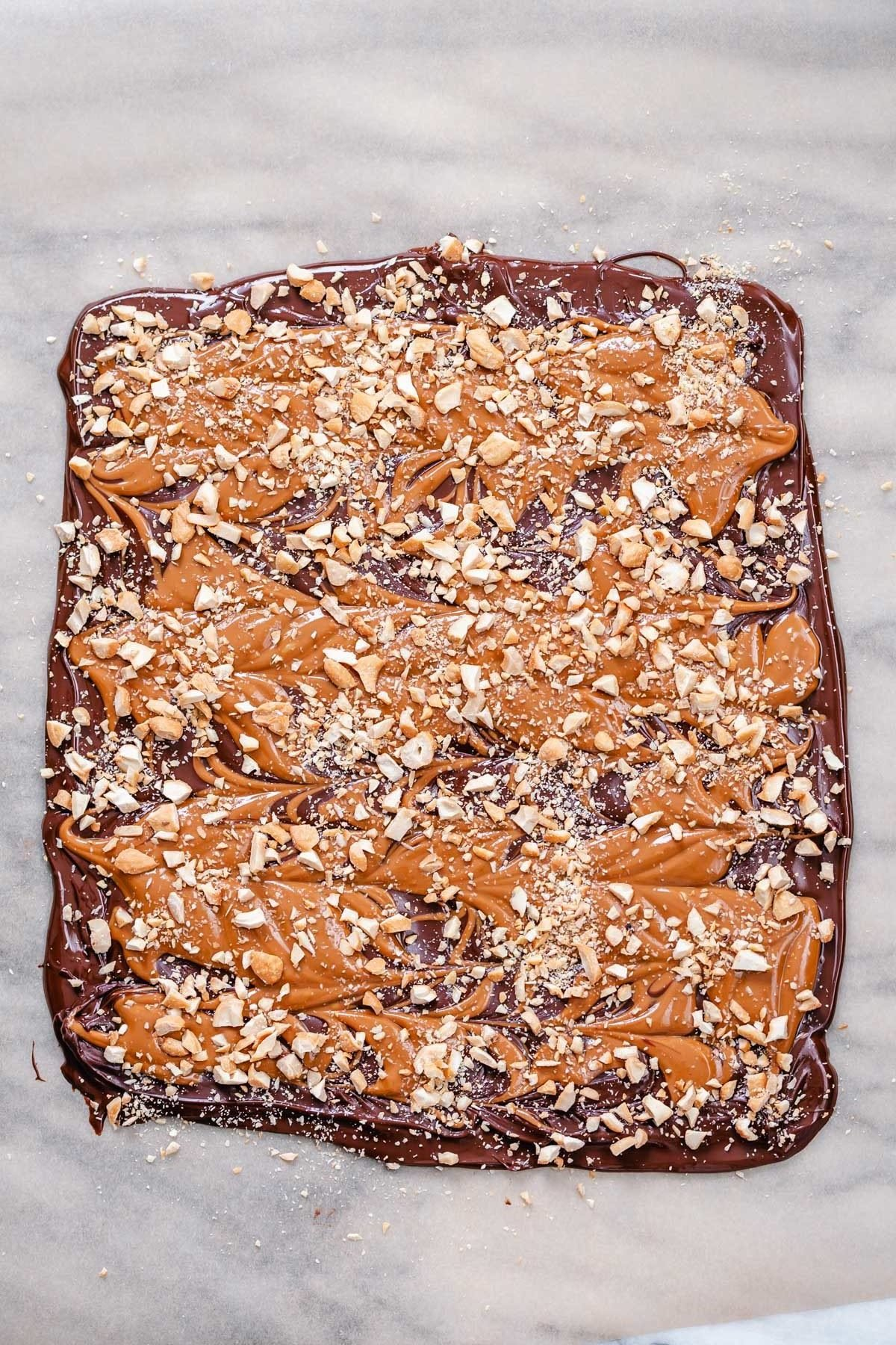 overhead shot of set vegan peanut butter cup chocolate bark sprinkled with peanuts