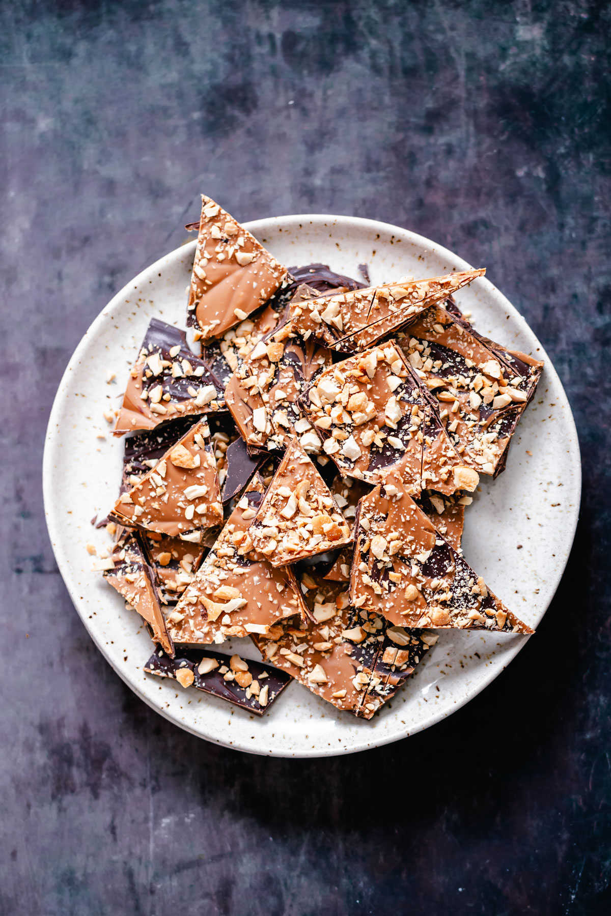 vegan dark chocolate and peanut butter bark with chopped peanuts on a white plate