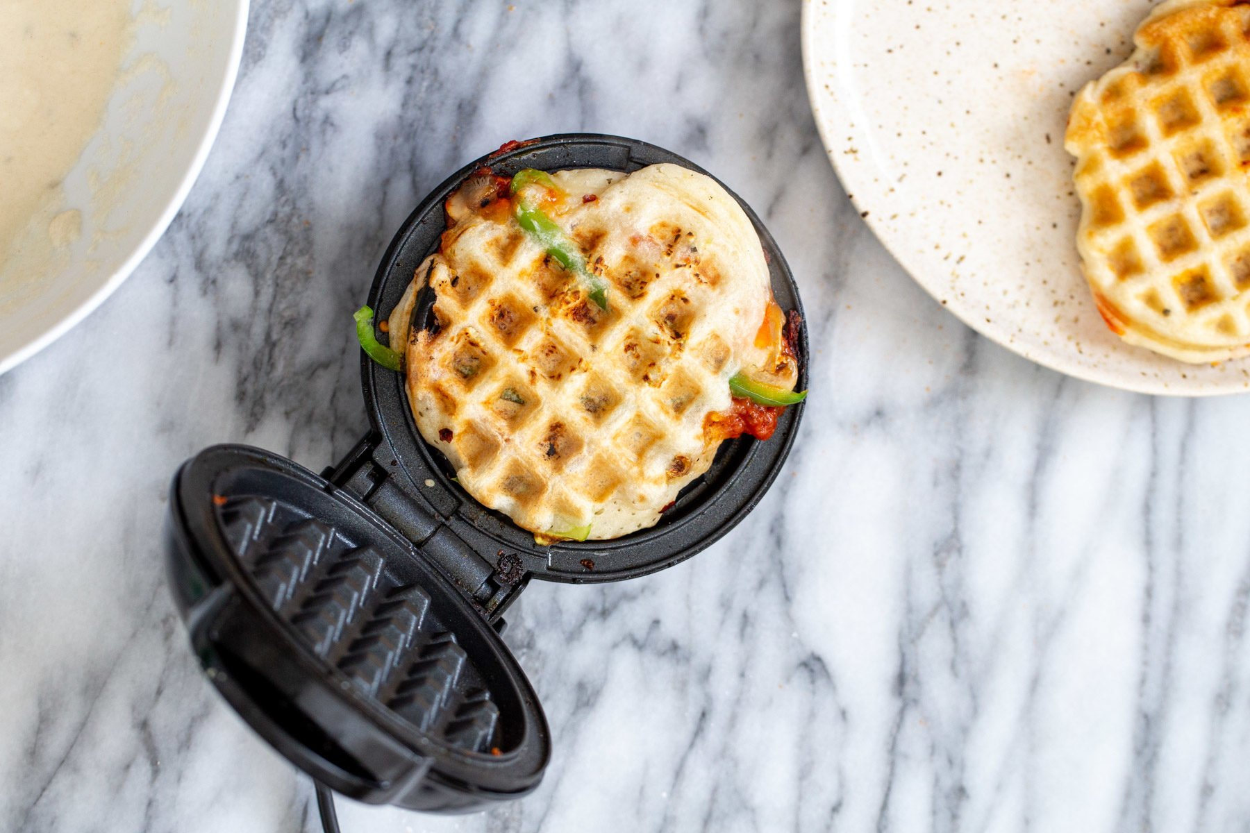a freshly baked vegan pizza waffle in a waffle iron