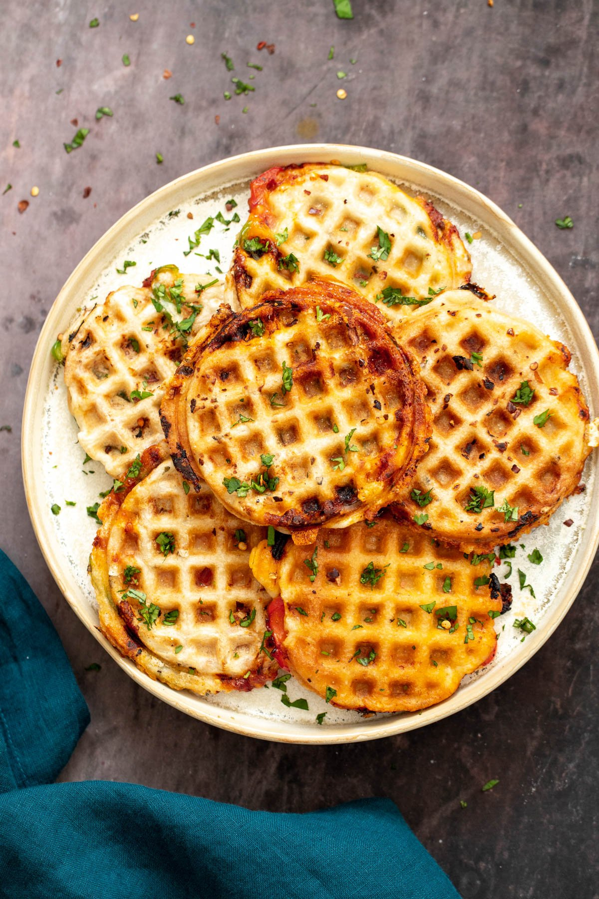 vegan pizza waffles on a white plate with a napkin on the side