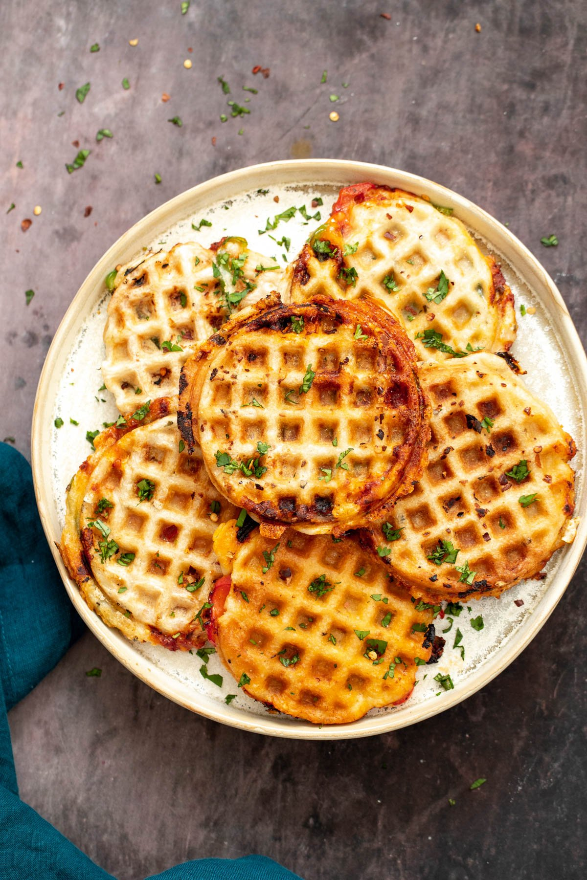 a plate with homemade vegan pizza waffles sprinkled with herbs