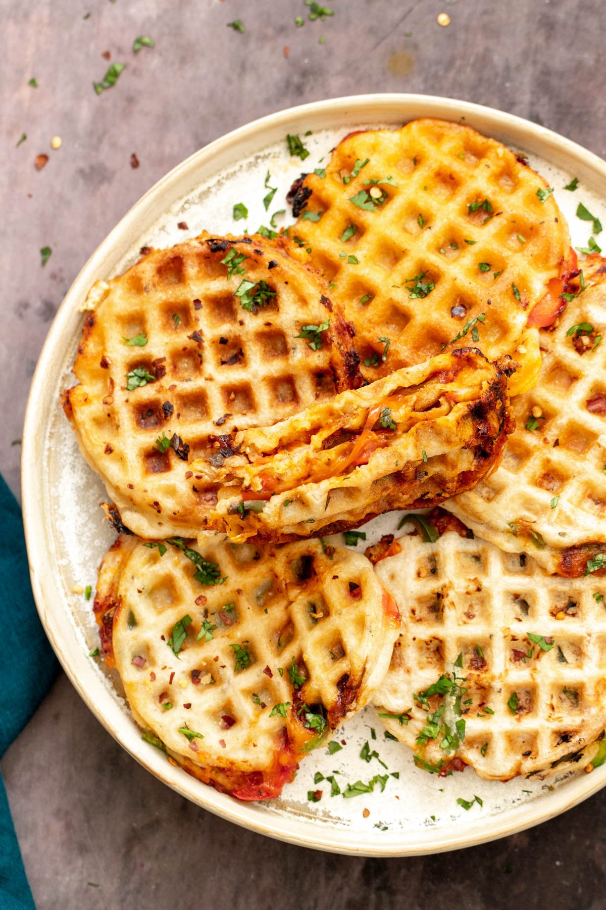 a plate with freshly baked vegan pizza waffles with one waffle being cut into half to reveal cheesy filling