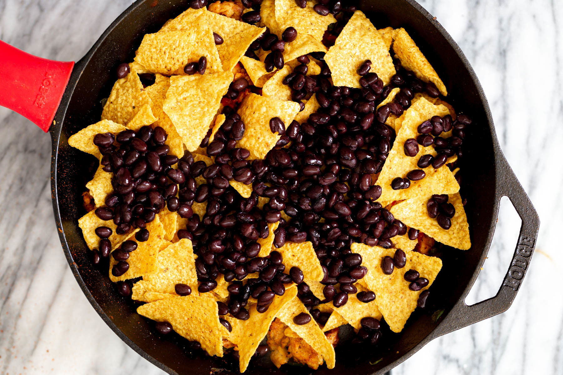 black beans being added on top of tortilla chips for making enchiladas