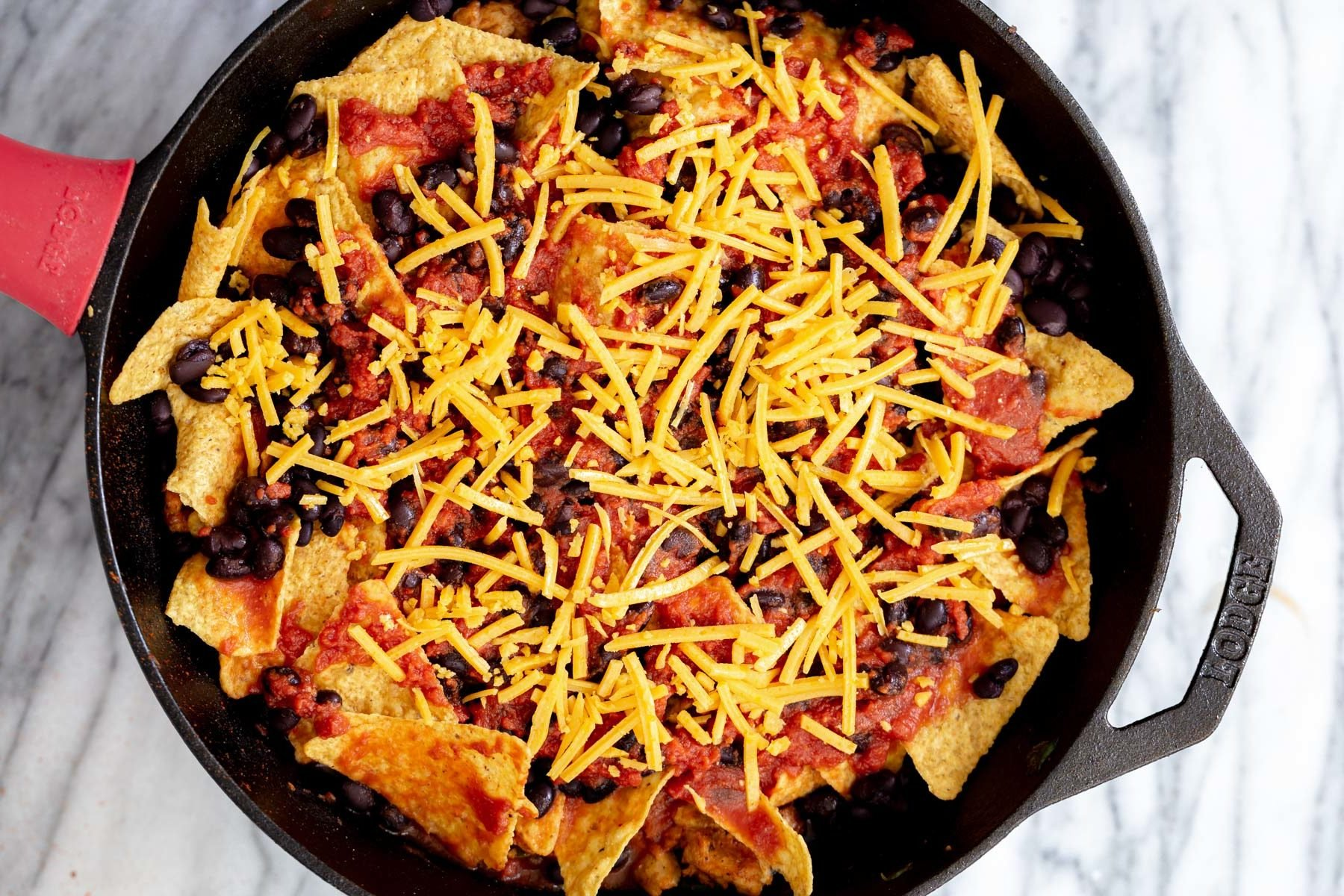 vegan skillet enchiladas being topped with vegan cheese shreds