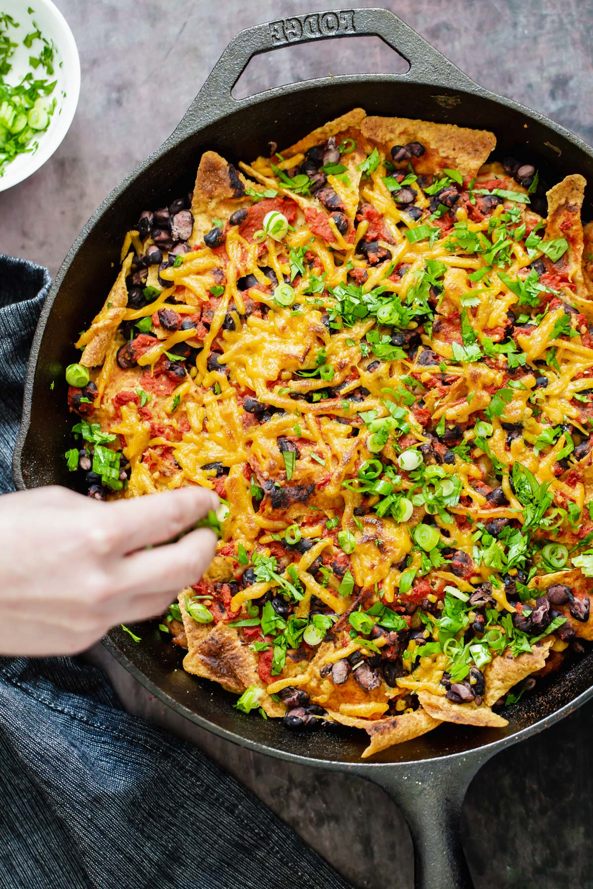a hand reaching for a serving of vegan skillet enchiladas with black beans