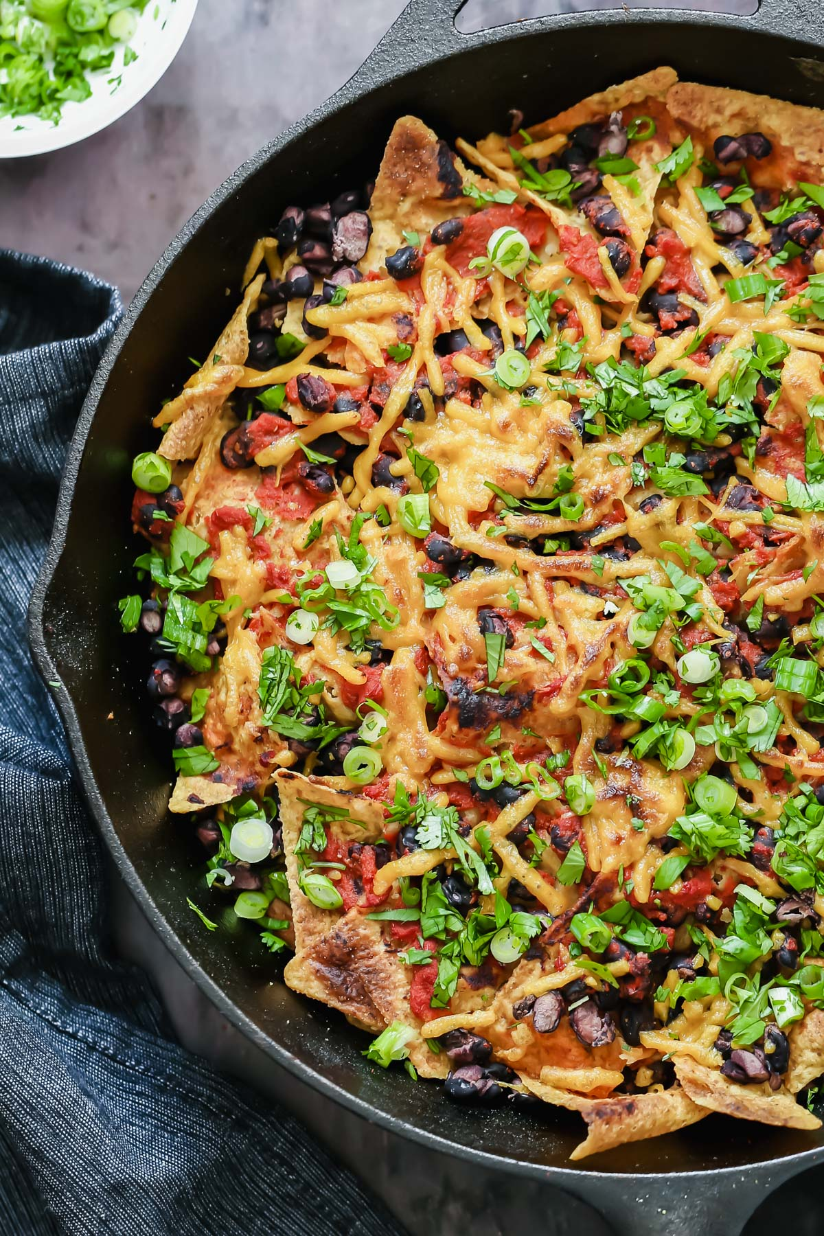 close-up overhead shot of vegan skillet enchiladas with tortilla chips, black beans and soy curls