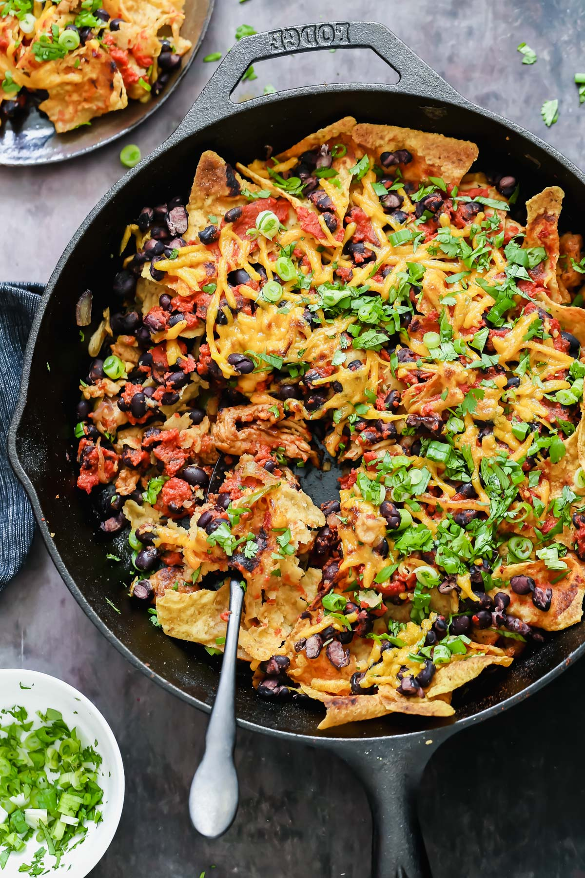 overhead shot of a vegan skillet nachos topped with vegan cheese shreds and green onions