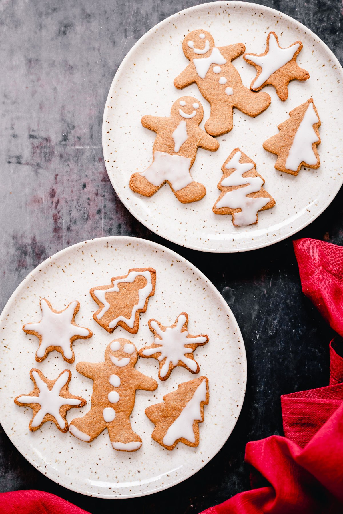 two plates with vegan iced gingerbread cookies