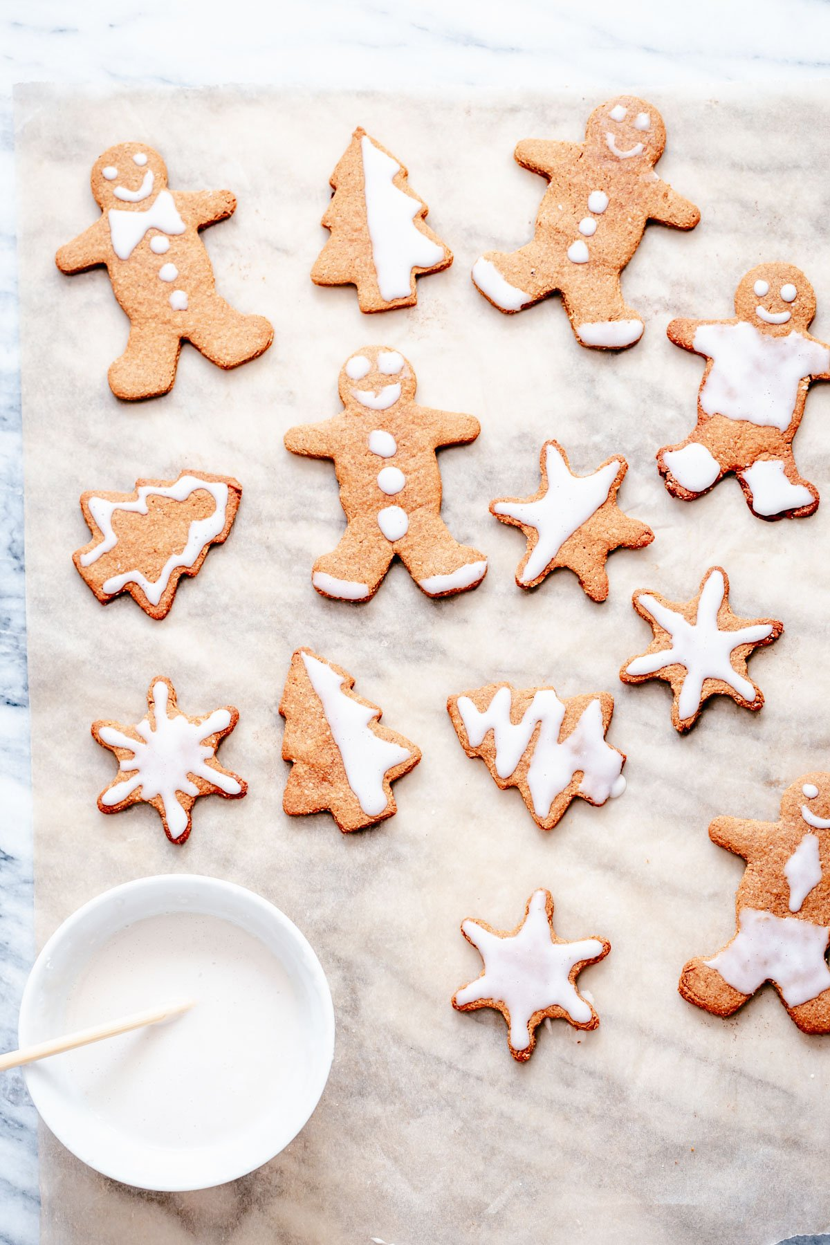 iced vegan gingerbread men, stars and tree shaped cookies on a sheet of parchment paper