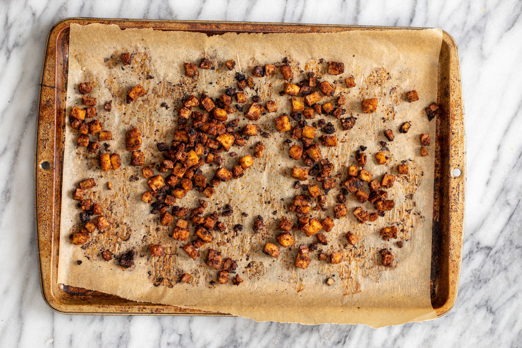 crispy smokey oven roasted tofu cubes on a baking sheet