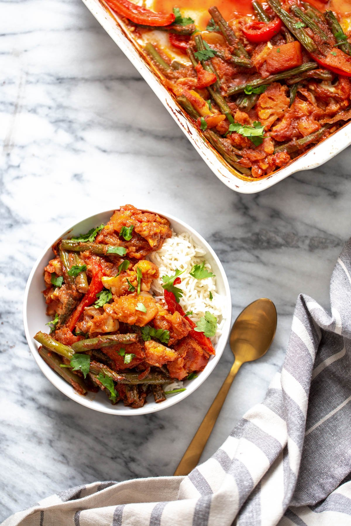 vegan curry vegetable casserole served with a side of rice and sprinkled with. coriander seeds