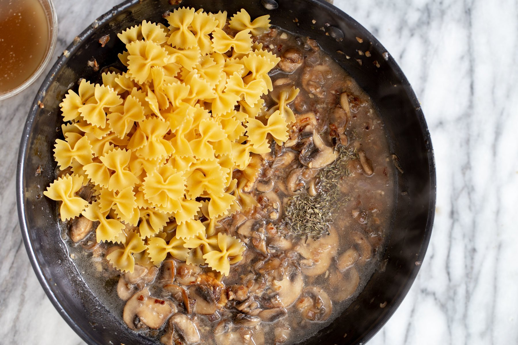 farfalle pasta being added to a pan with mushroom sauce