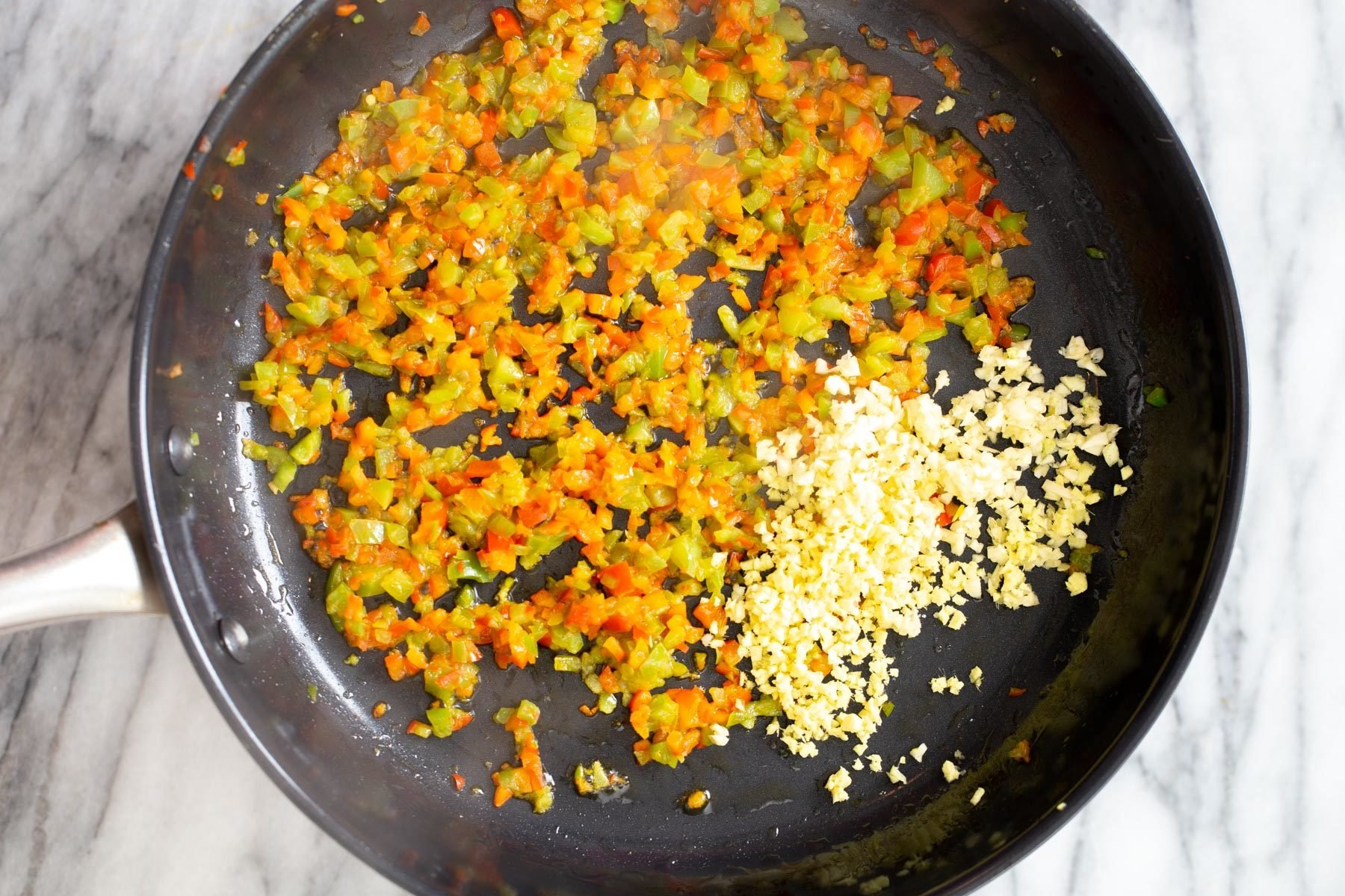minced garlic being added to frying pan