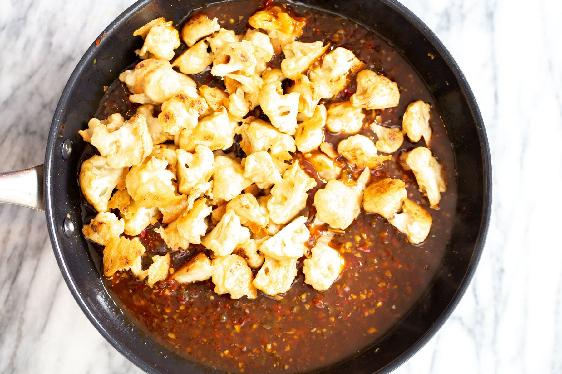 breaded baked cauliflower getting tossed with general tso sauce