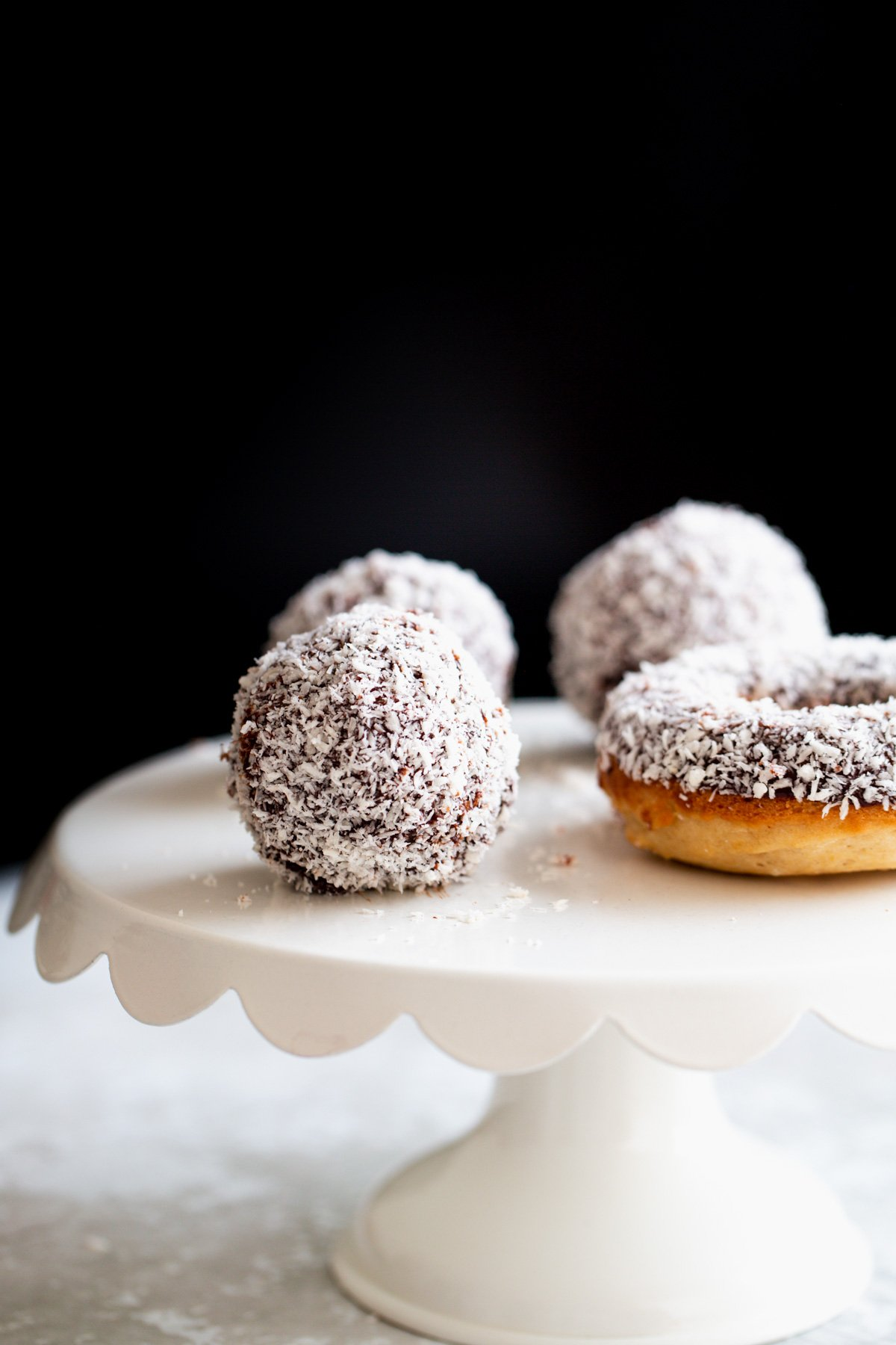 vegan lamington donut holes and baked donuts on a white cake stand
