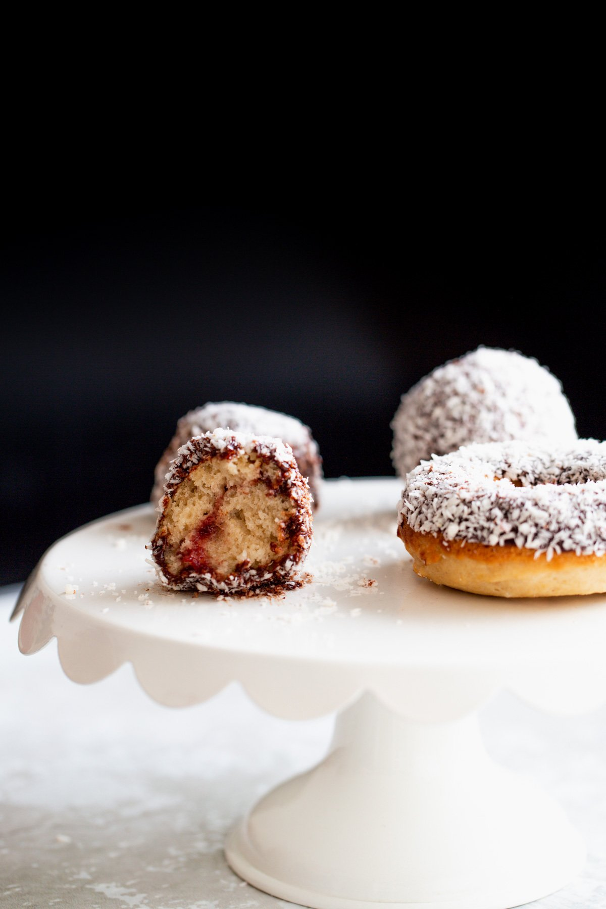 side view of a vegan lamington donut hole with one bite taken