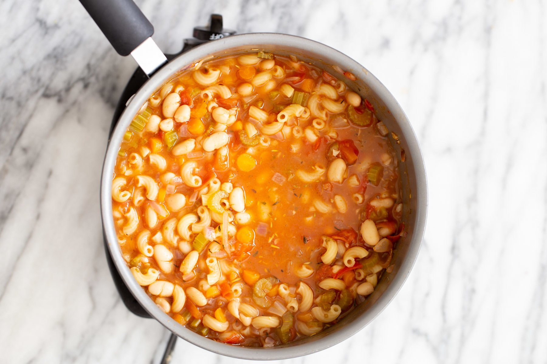 pasta and white beans simmering in tomato broth in a saucepan