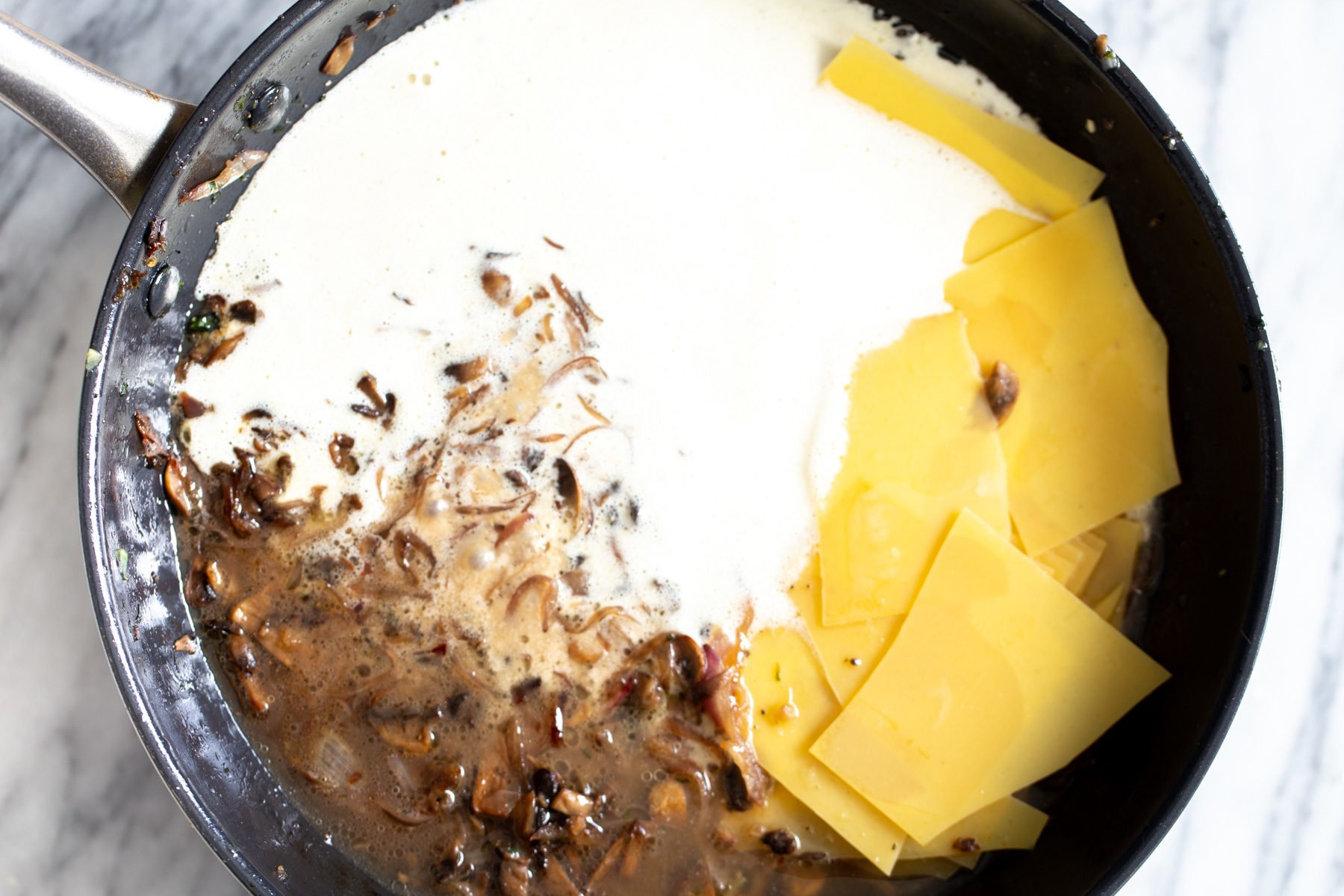 alfredo sauce and lasagna sheets being added to skillet to make skillet lasagna