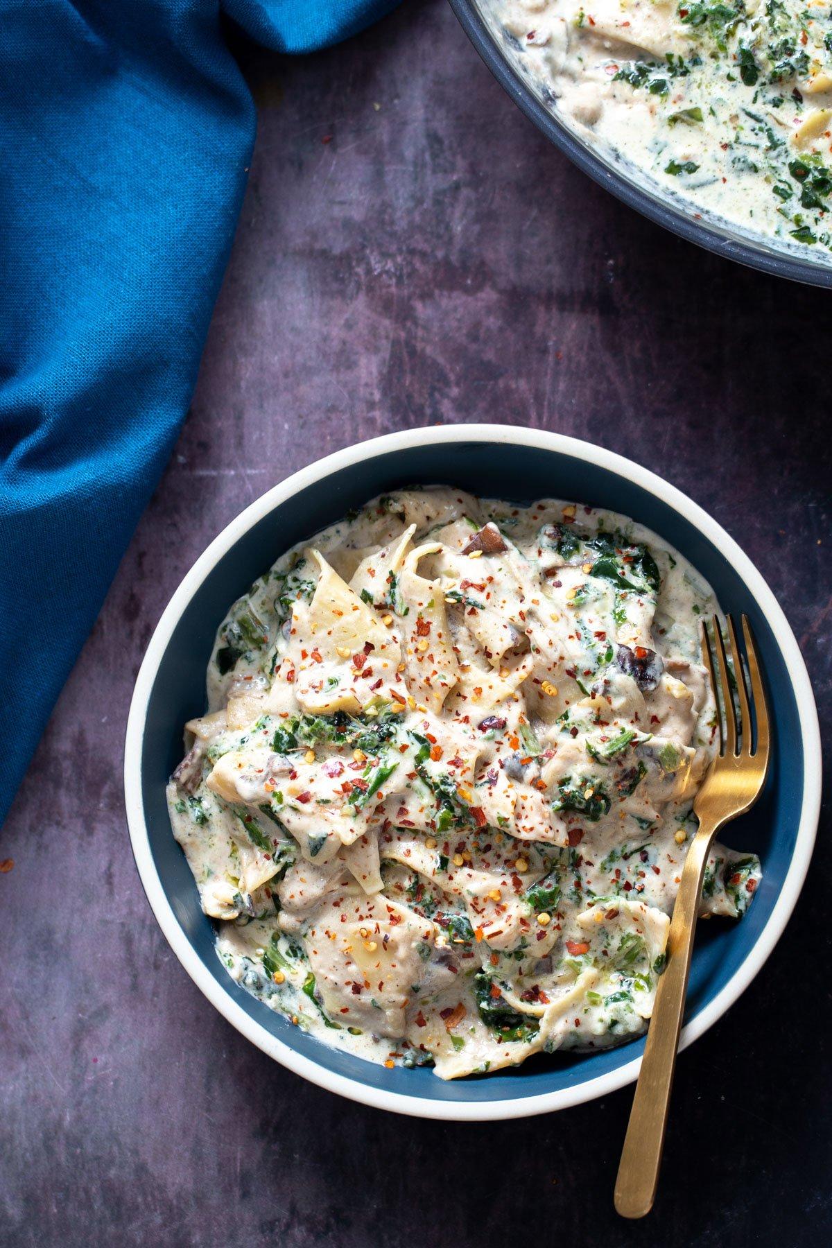 a blue bowl filled with vegan alfredo skillet lasagna