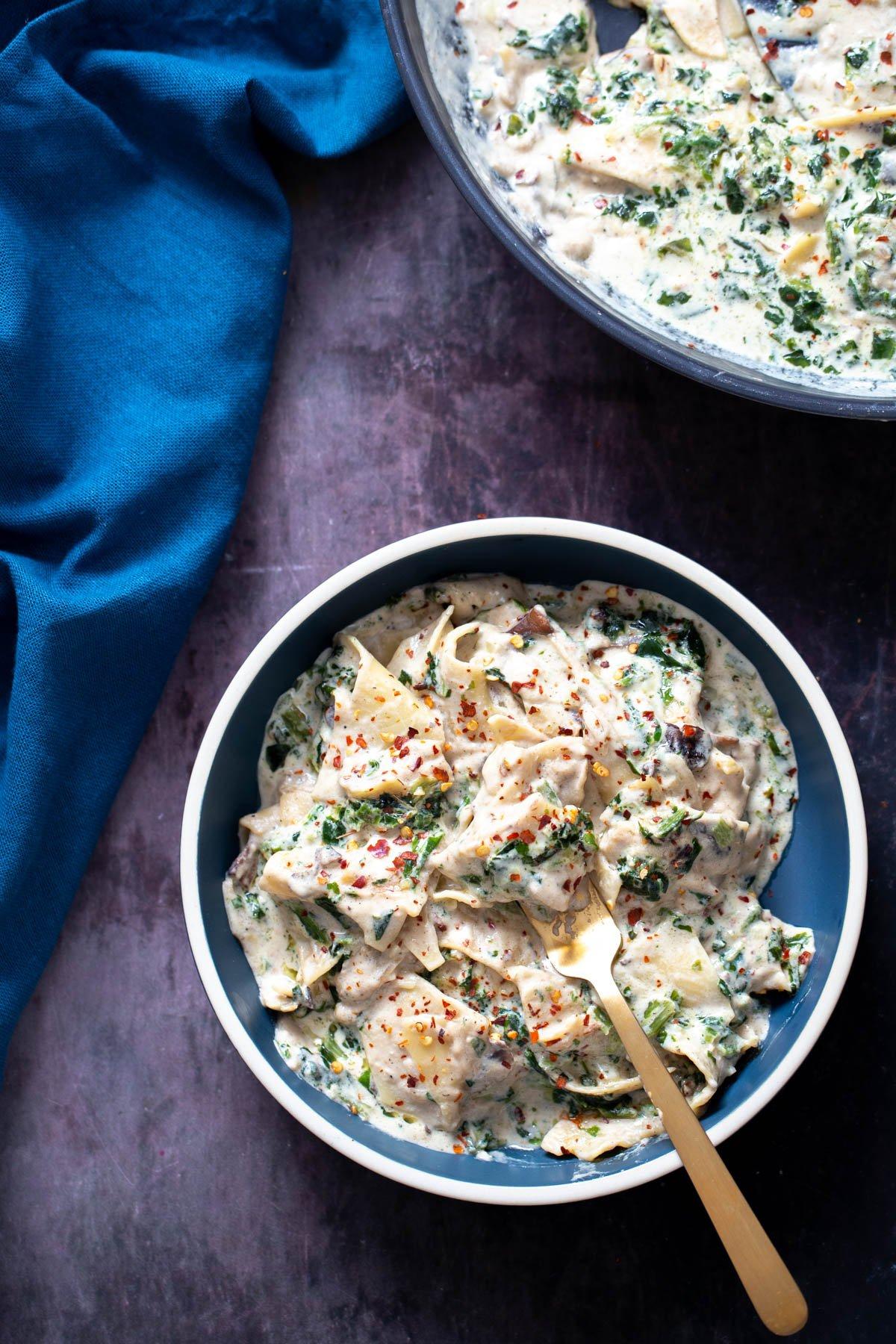 a serving of vegan mushroom spinach skillet lasagna served in a bowl with a golden fork