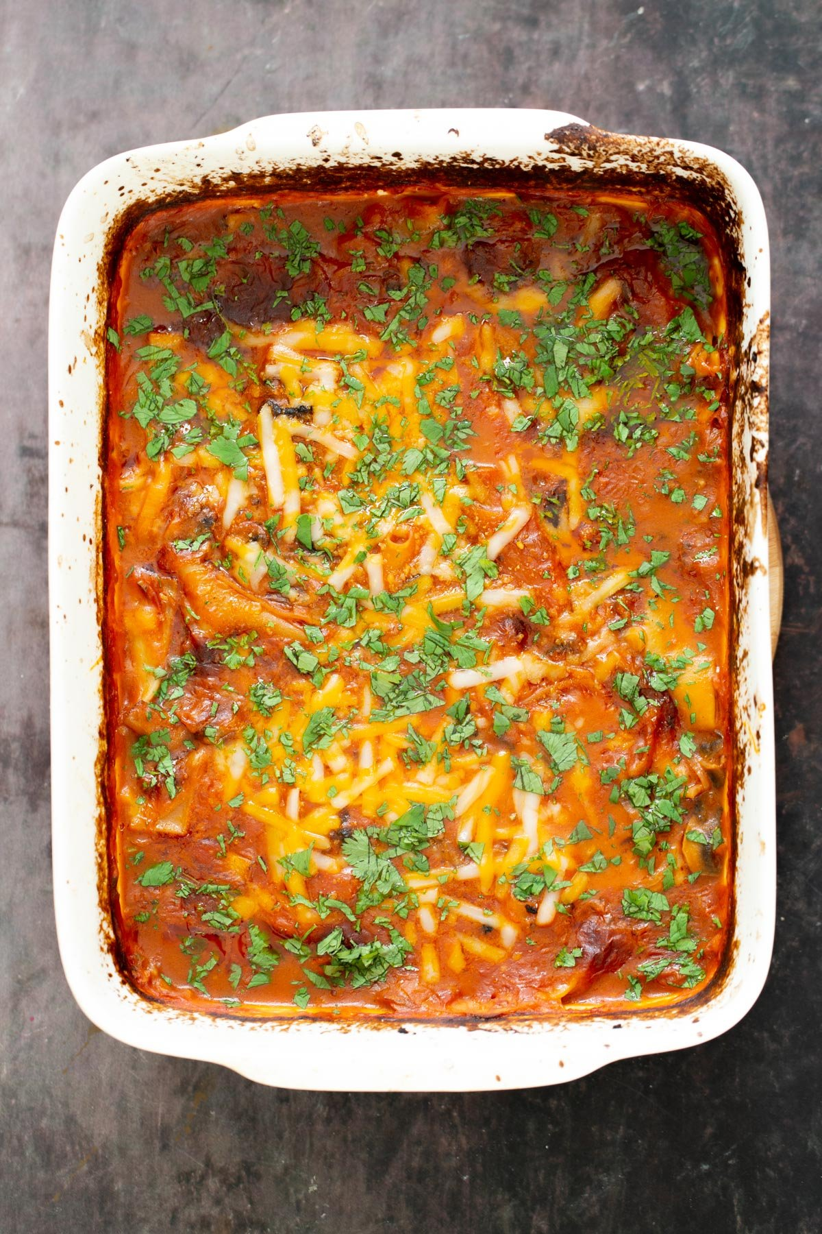 a casserole dish with vegan butter chicken lasagna bake sprinkled with chopped cilantro