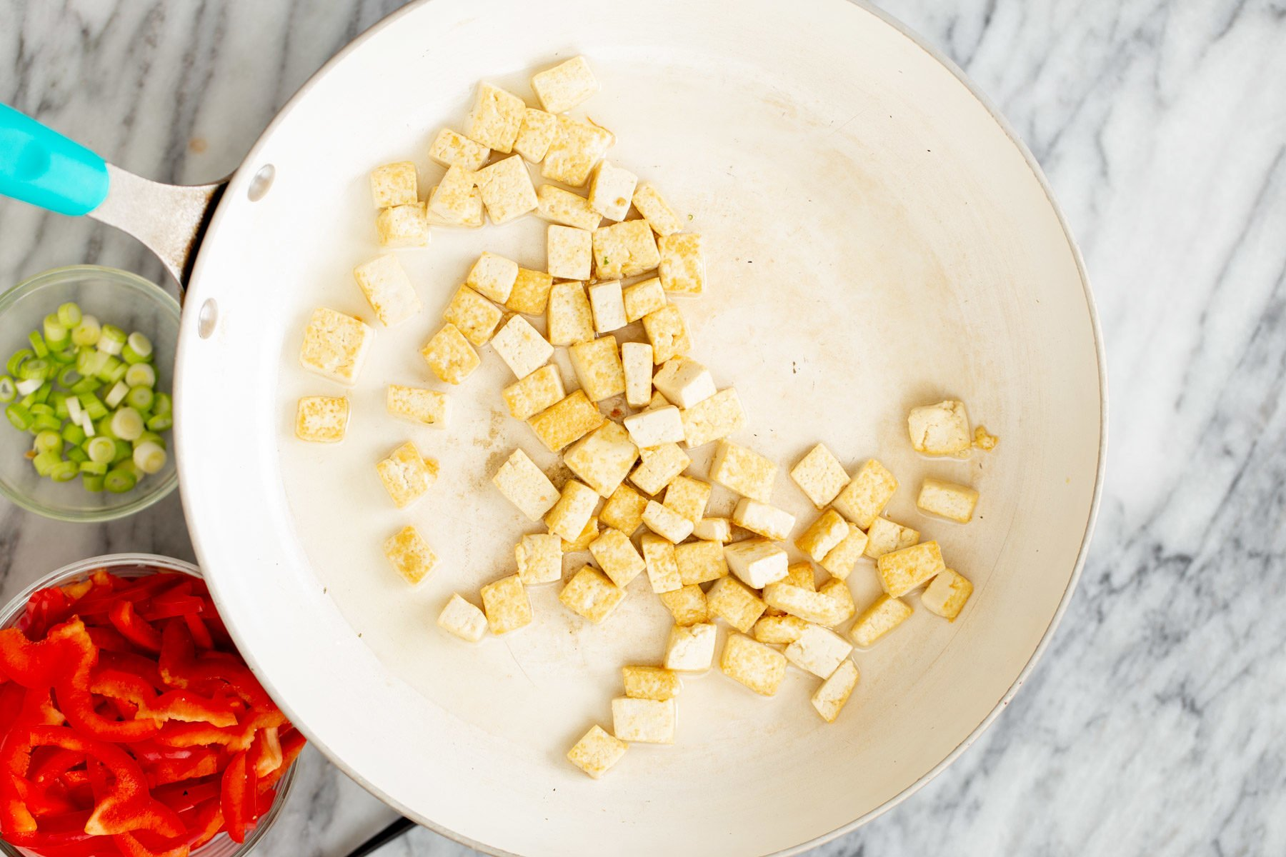 pressed tofu cubes being fried until golden in a white pan