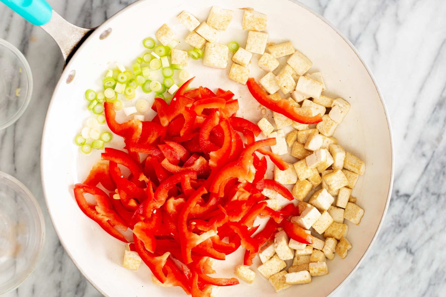 sliced bell peppers, green onion and tofu cubes being fried in a sauteeing pan