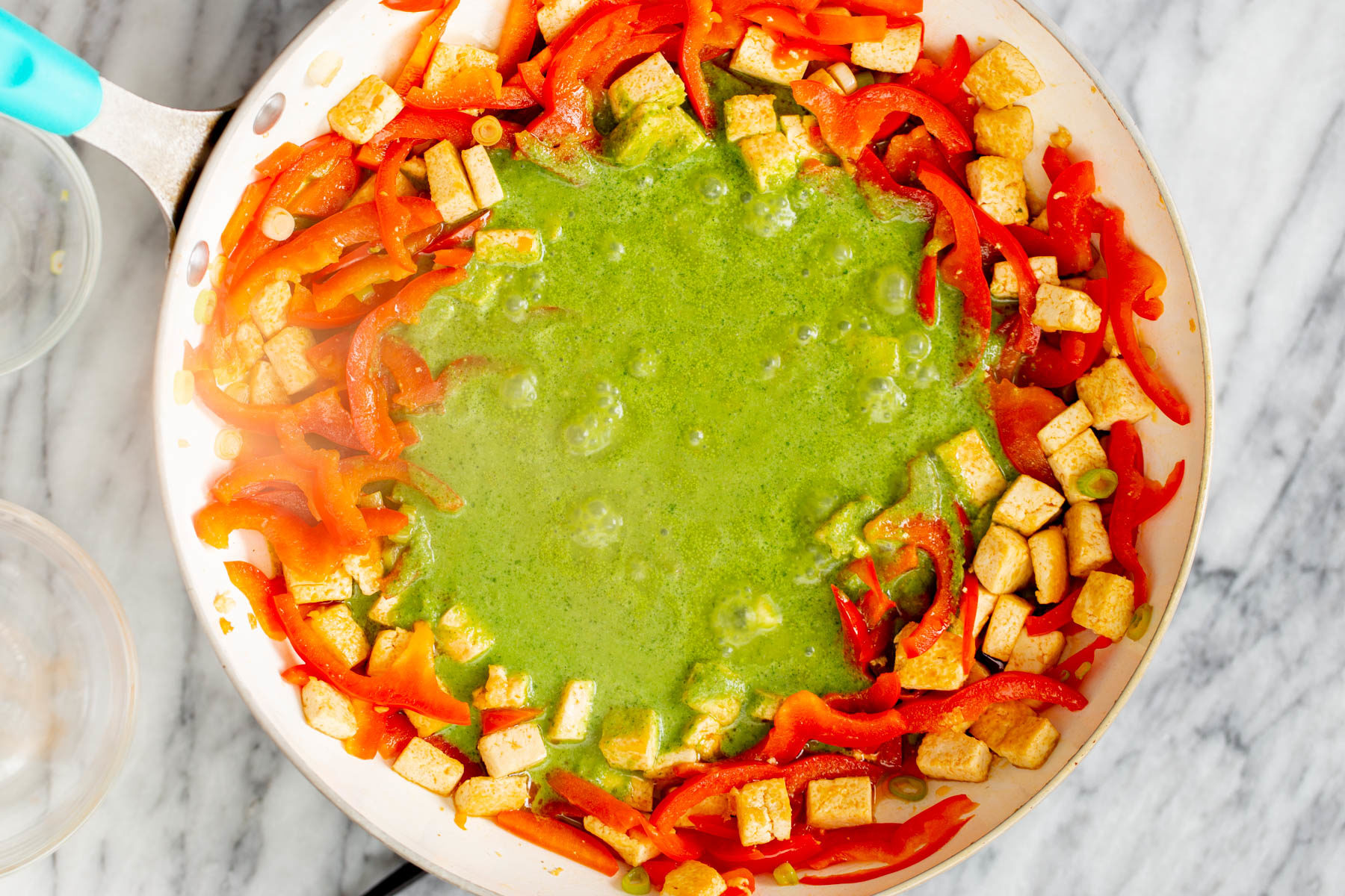 green curry sauce being poured into a frying pan with sauteed bell peppers and tofu cubes