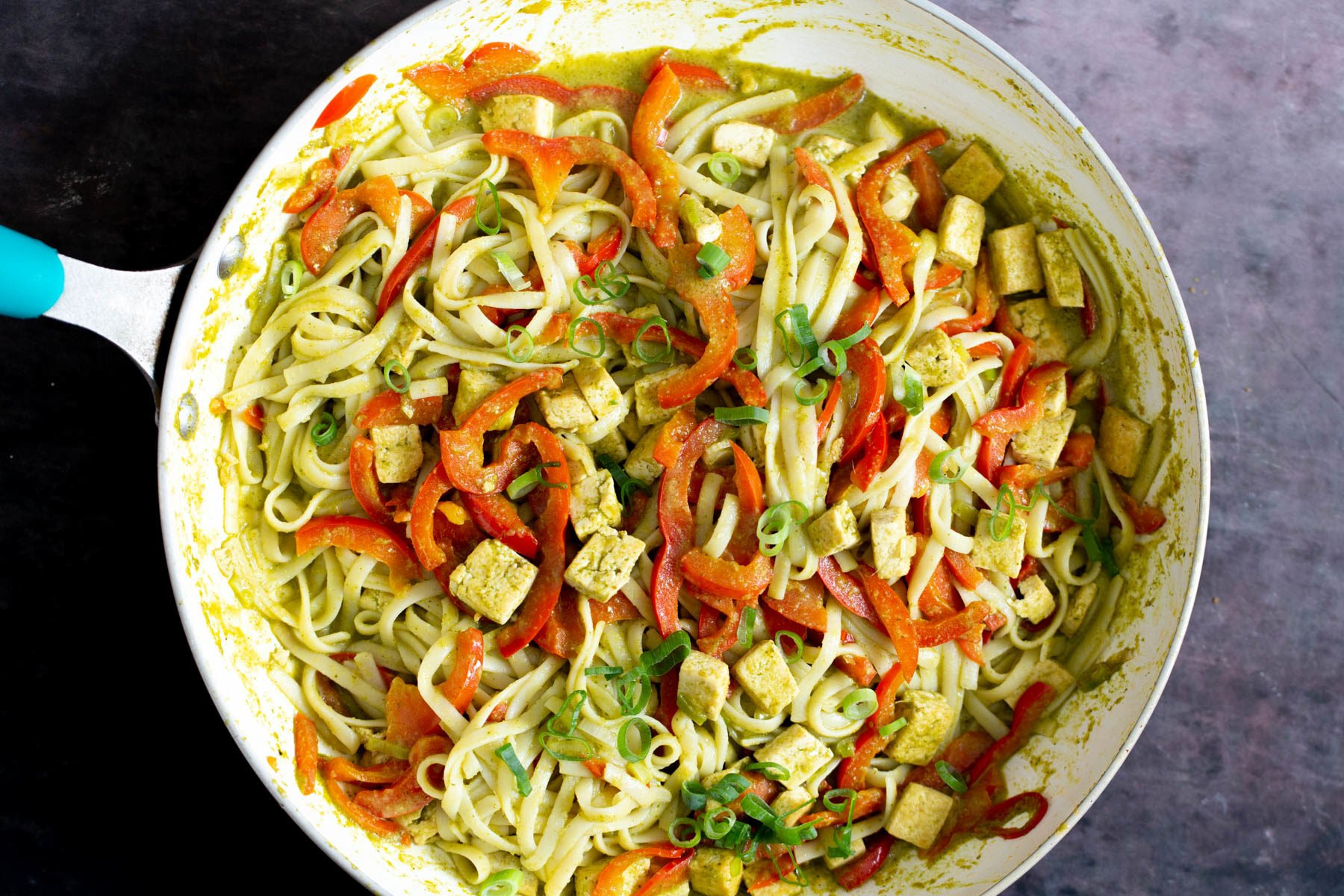 rice noodles being tossed in a pan with sauteed veggies, tofu and green curry sauce