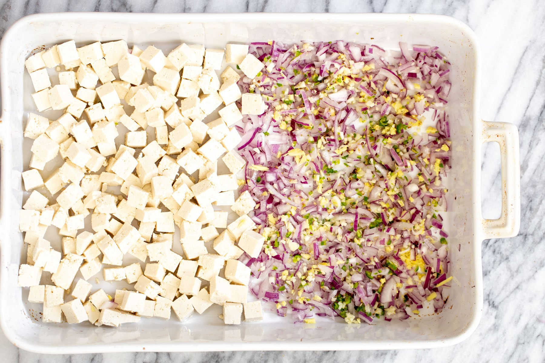 tofu cubes in a casserole dish next to minced onion, ginger, garlic and chile