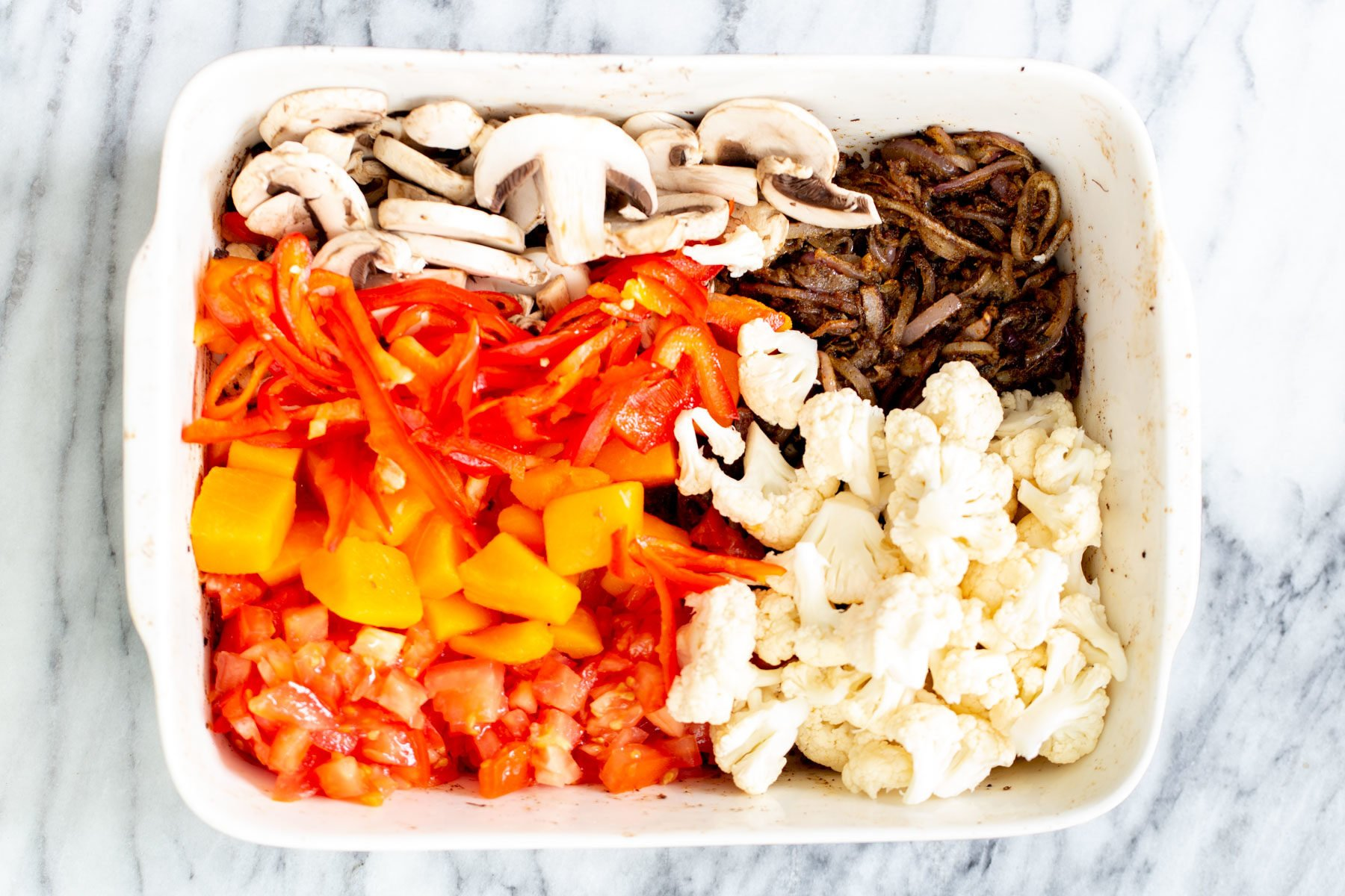 healthy vegetables assembled in a casserole dish to make balti vegetables